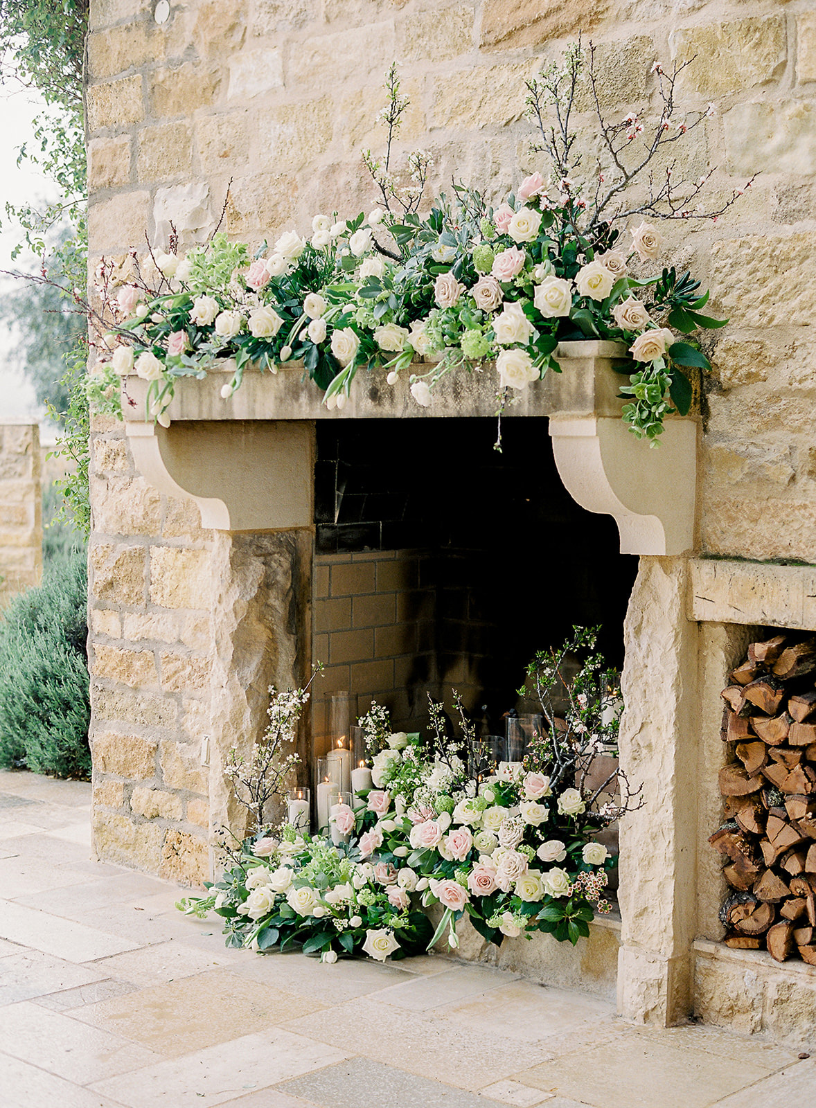 fireplace filled with floral and candle display