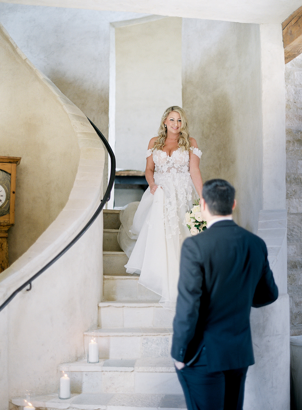 bride walking down staircase to groom for first look