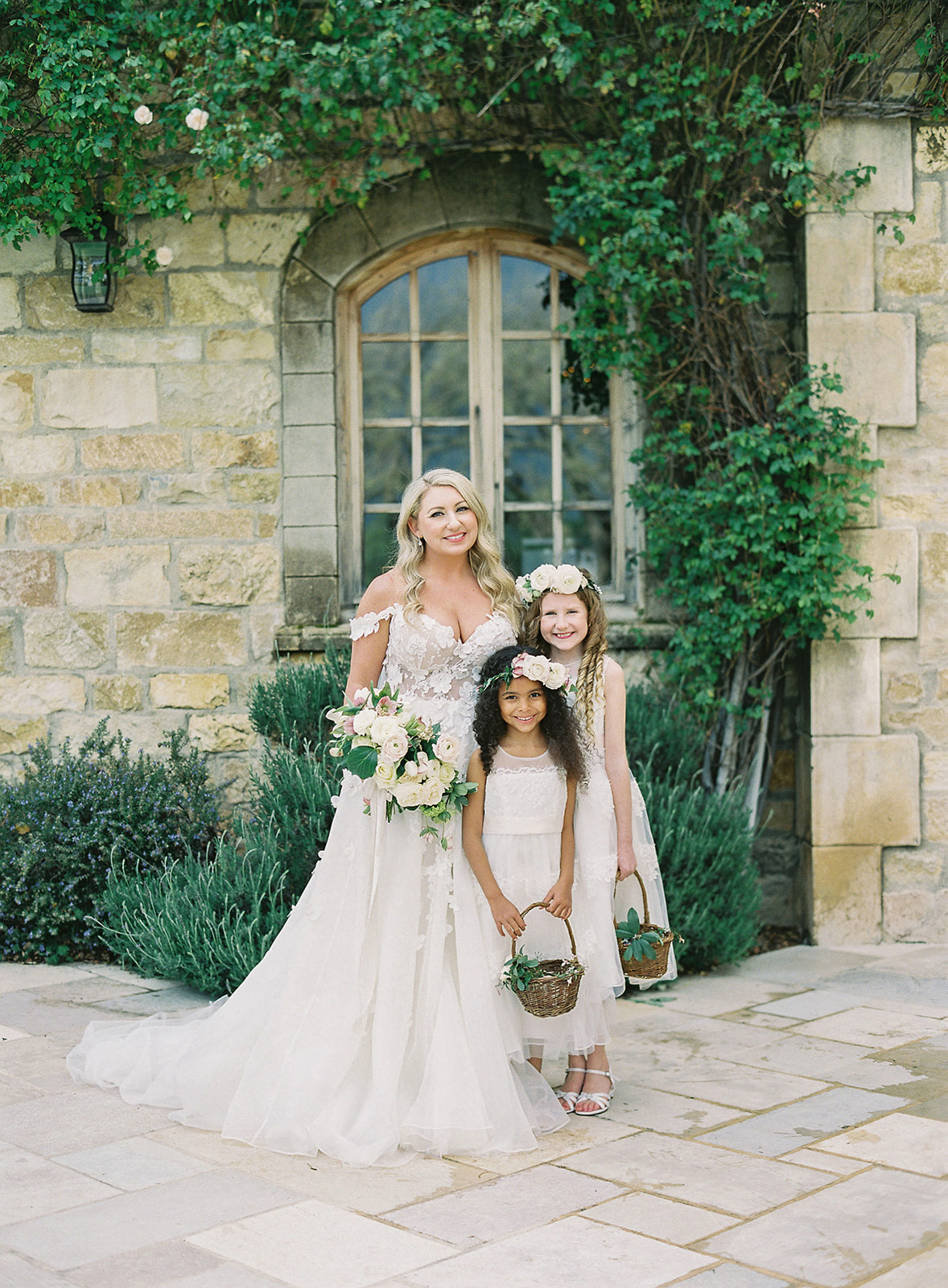 bride with two flower girls outside