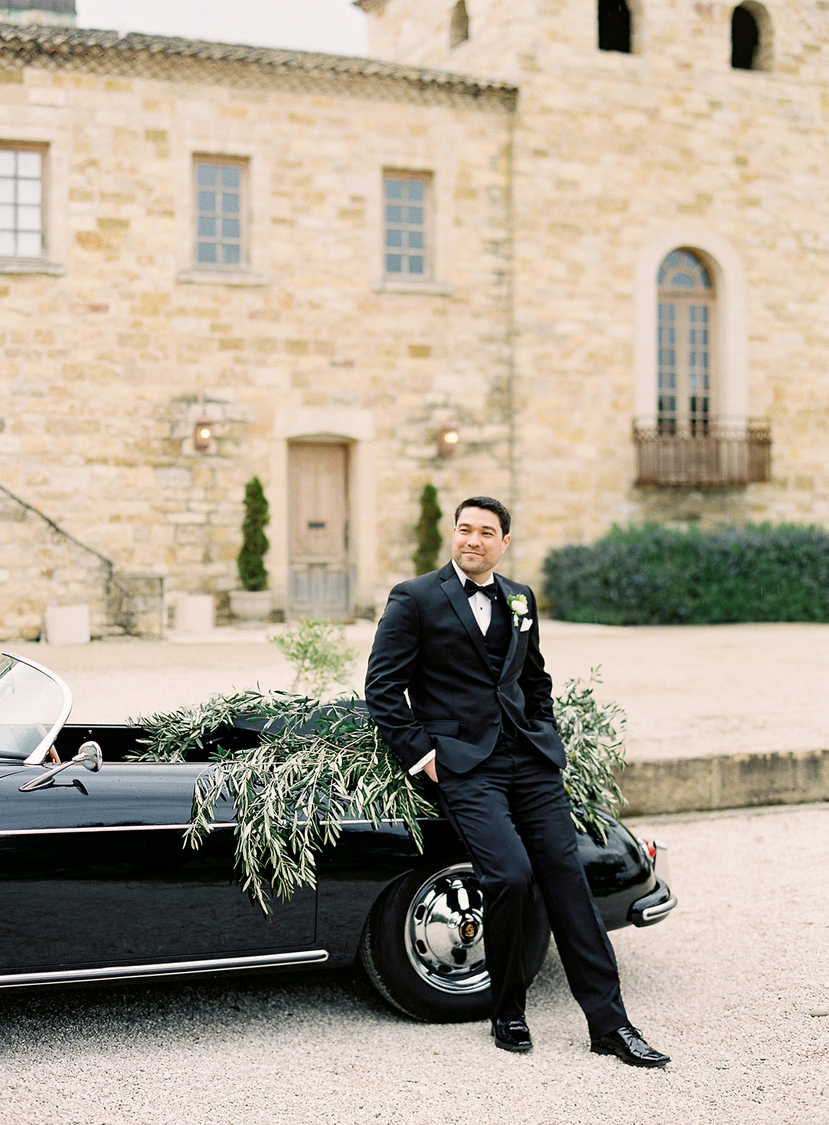 groom wearing black tux leaning on vintage car outside