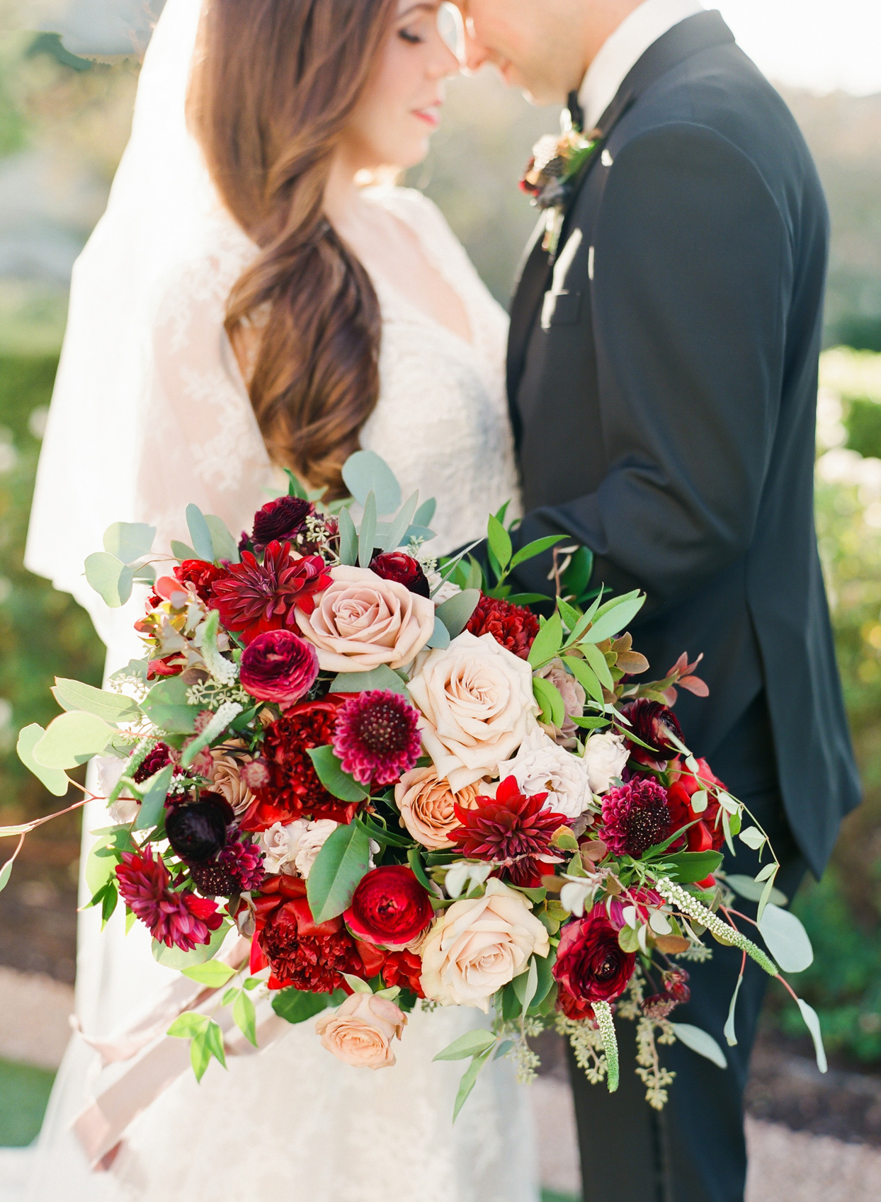 couple posing with lush red and pink floral bouquet