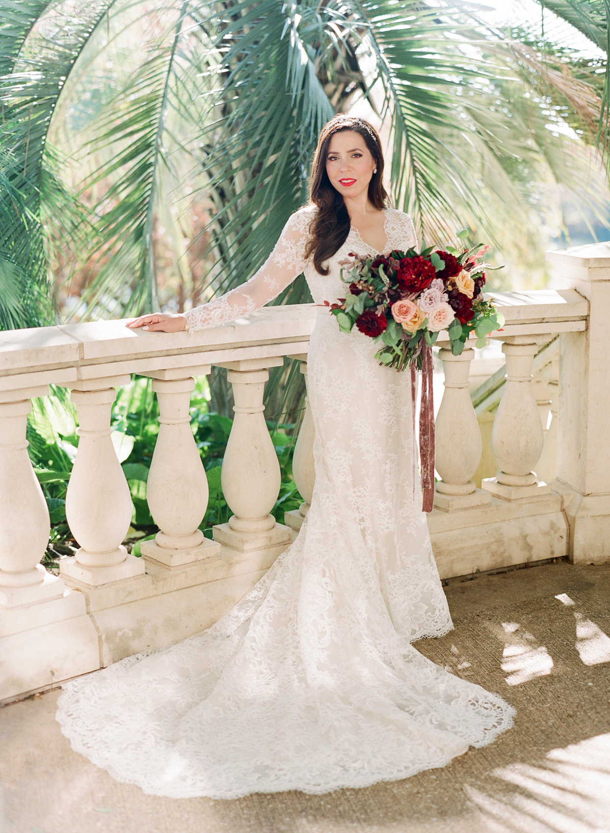 bride in white lace dress standing on balcony