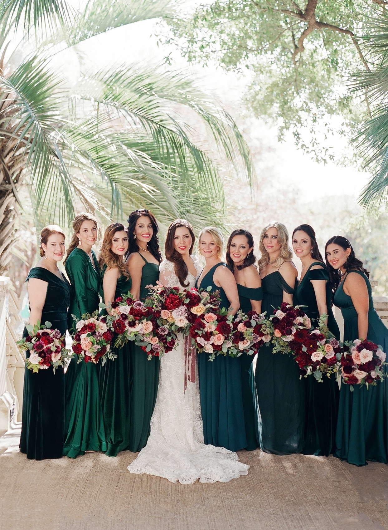 bridesmaids in deep green dresses with red bouquets