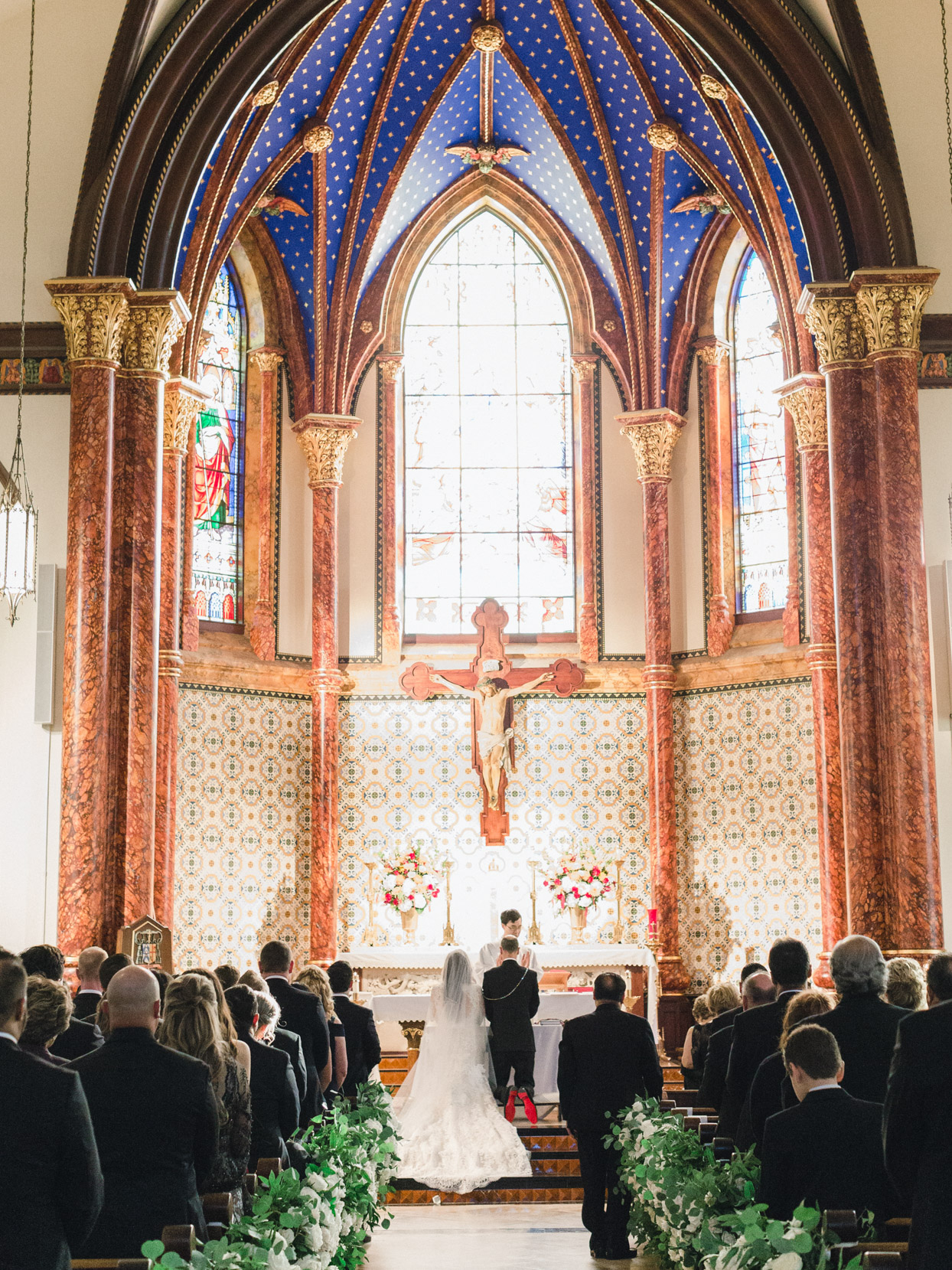 bride and groom kneeling during wedding ceremony at church
