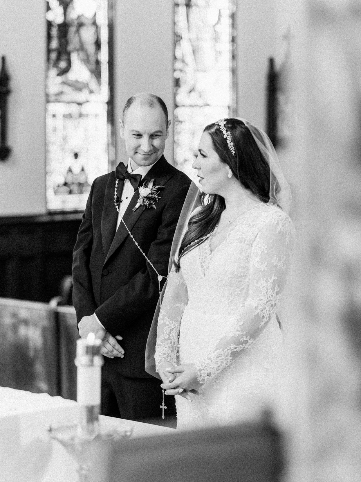 wedding couple smiling at each other during church ceremony