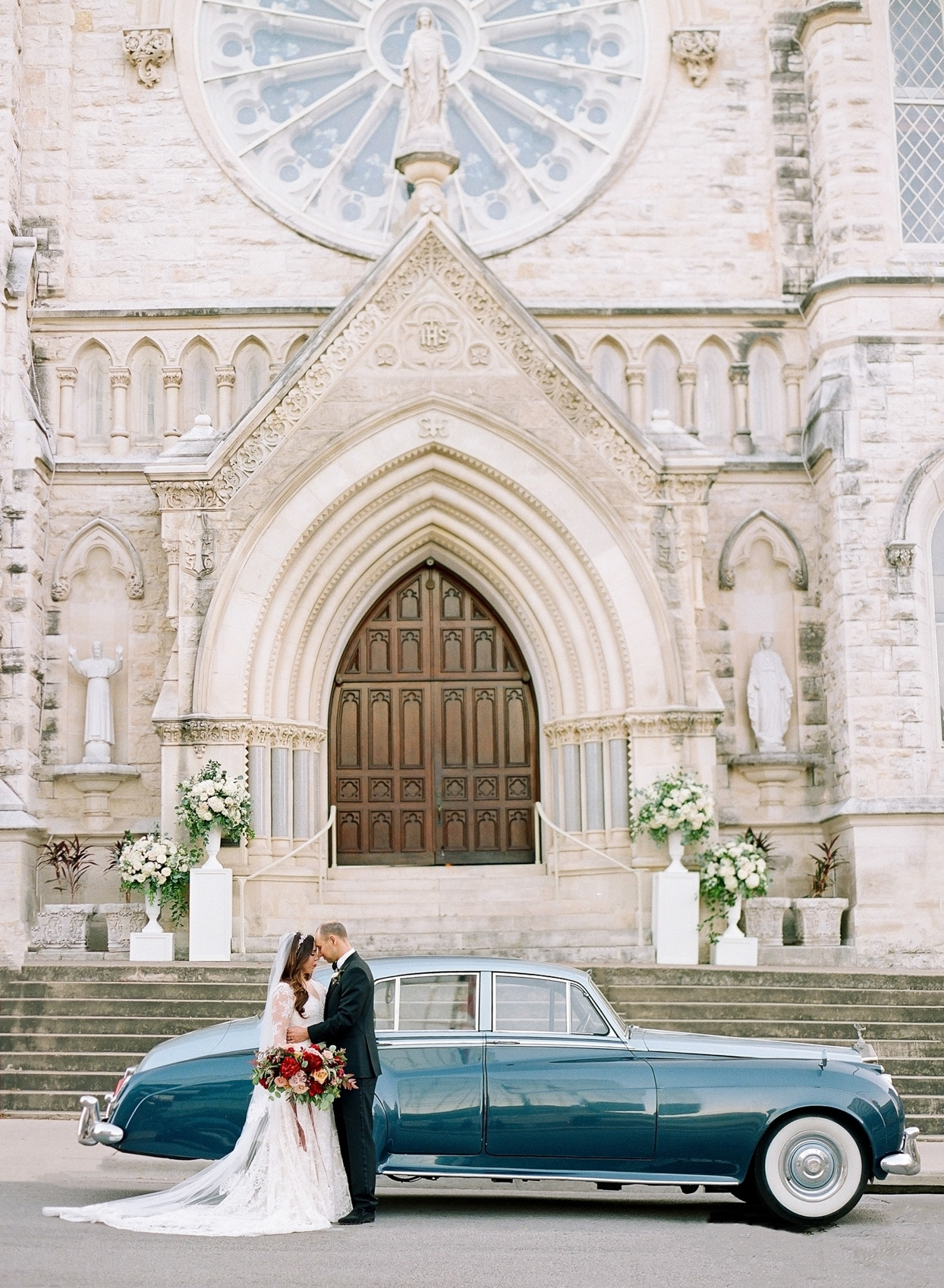 wedding couple posting in front of antique car and church