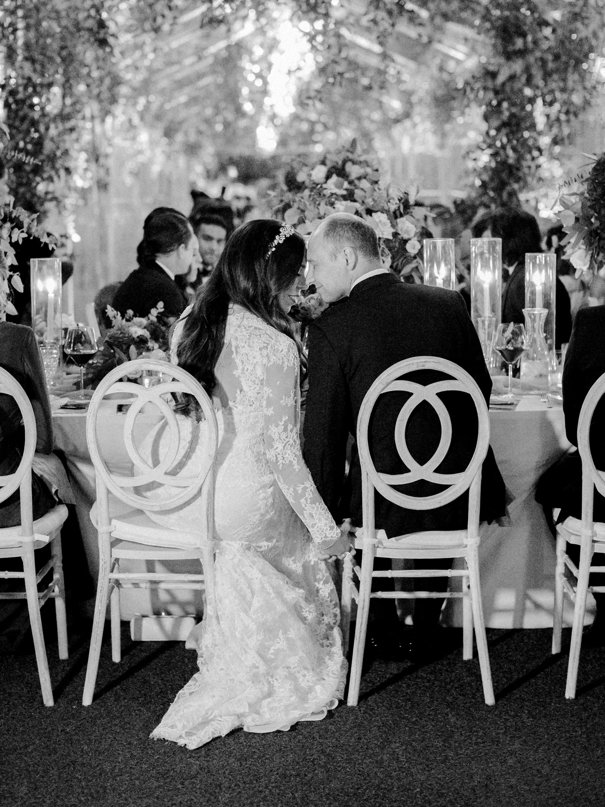 wedding couple holding hands and looking at each other during reception