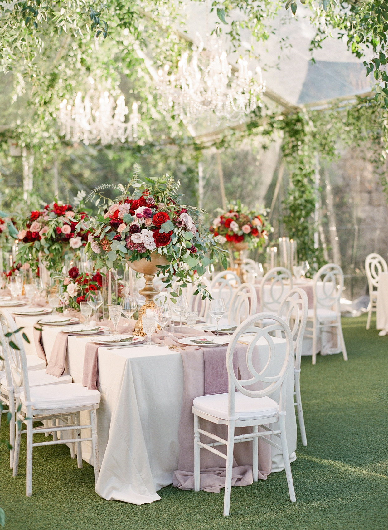 romantic white long tables with red floral centerpieces in wedding tent