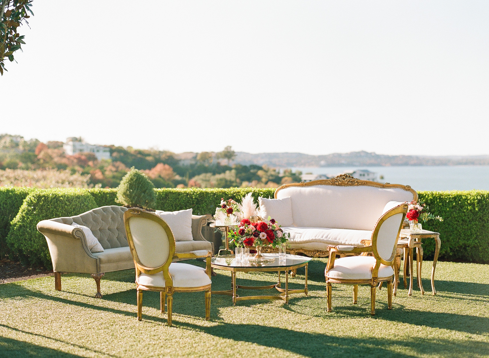 outdoor wedding lounge with antique pastel furniture with water view