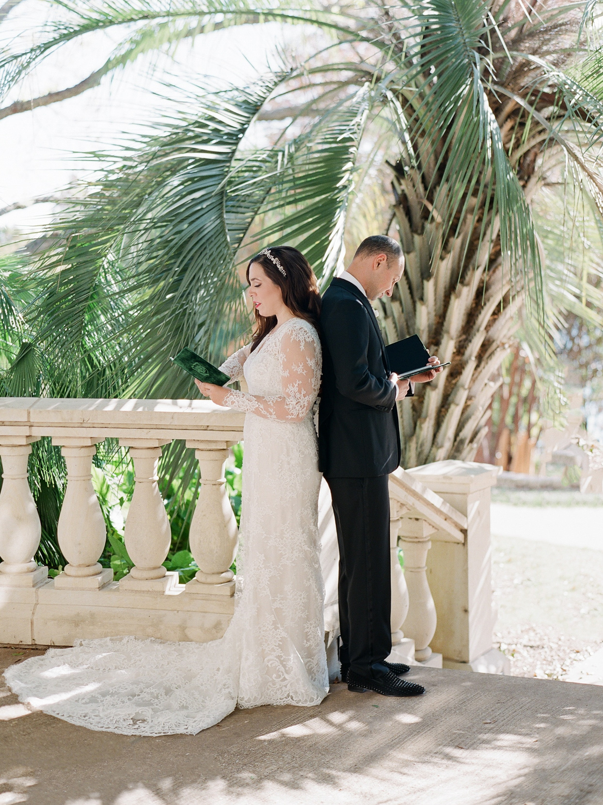 wedding couple standing back to back reading vows to each other
