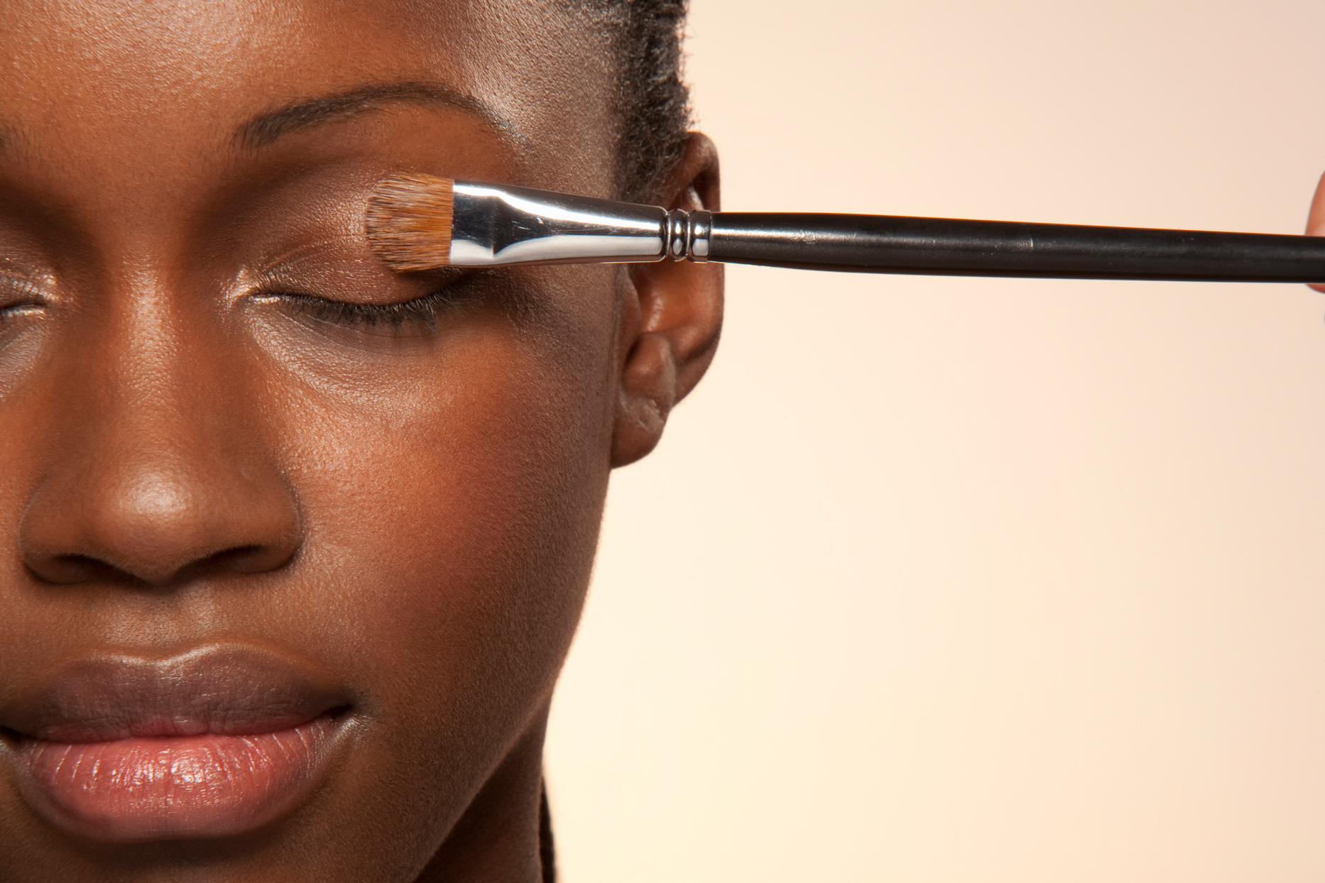 person applying eyeshadow primer with small black handle makeup brush