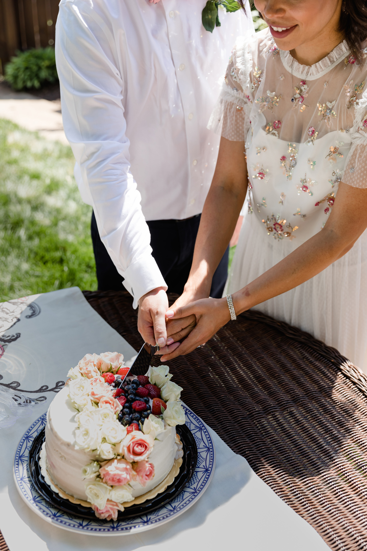 bride and groom cutting wedding cake topped with berries