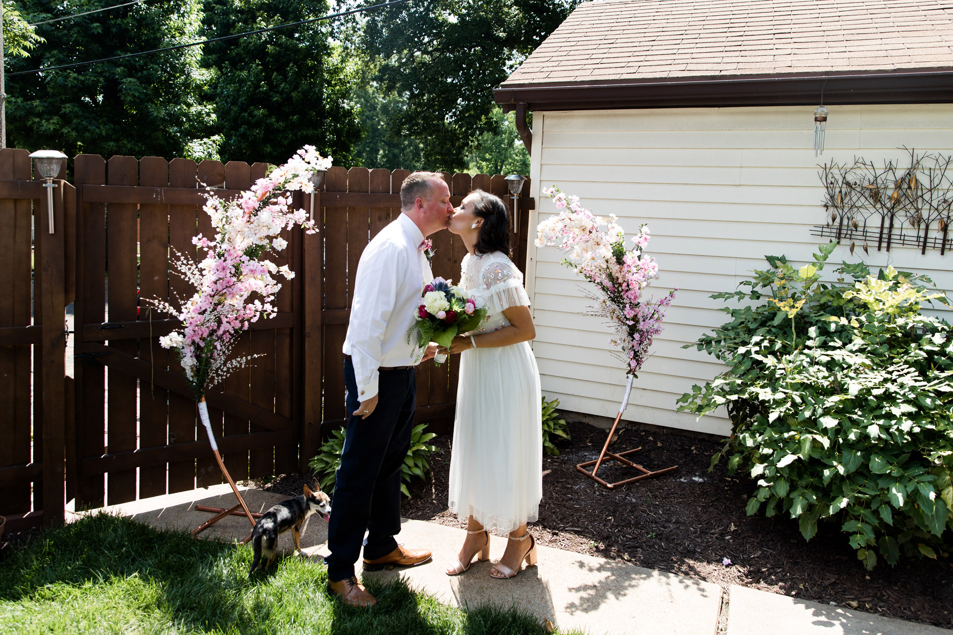 bride and groom sharing ceremonial kiss during backyard wedding