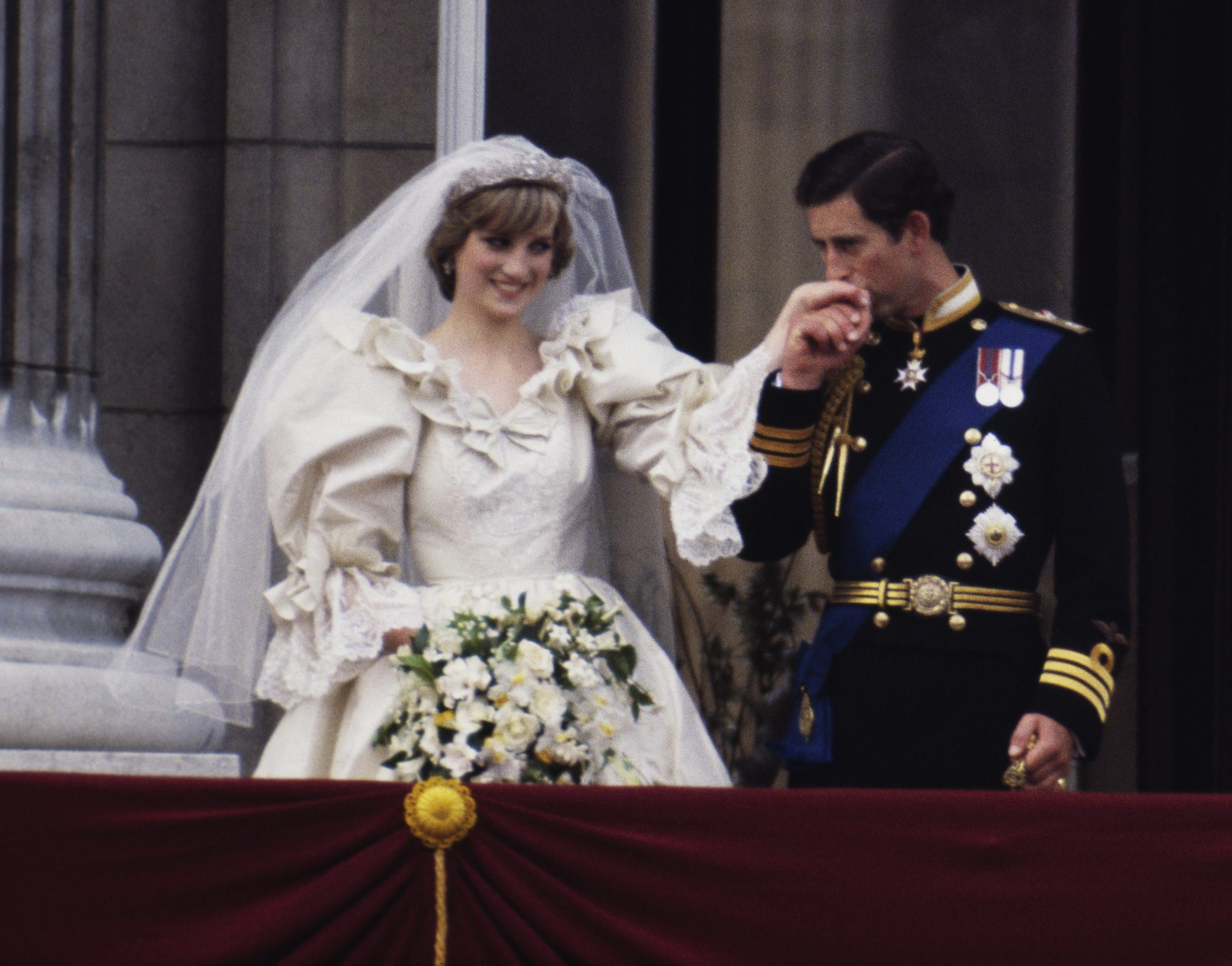 prince charles kissing princess diana's hand as she wears wedding dress after wedding