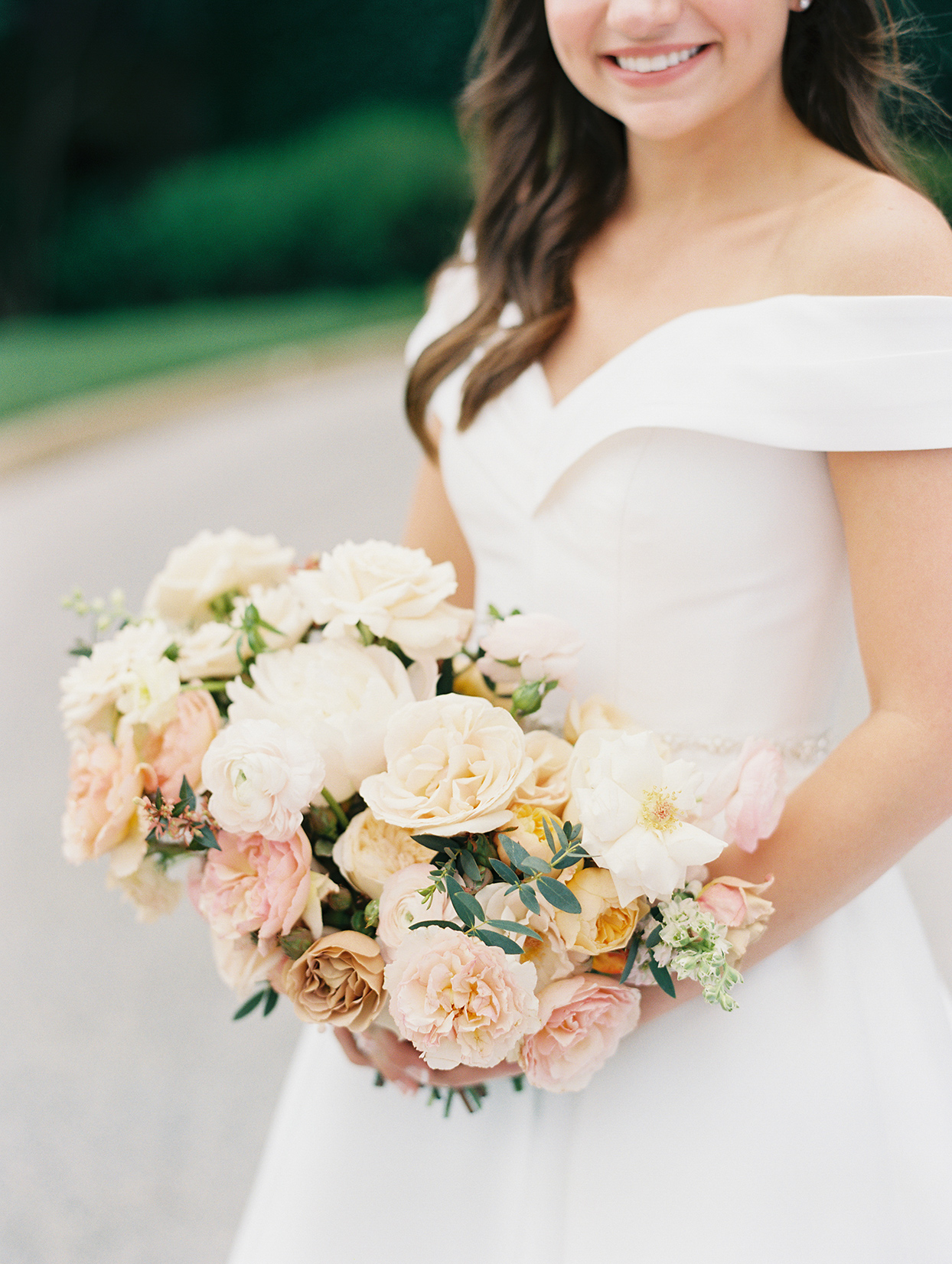 bride smiling holding blush toned floral bouquet