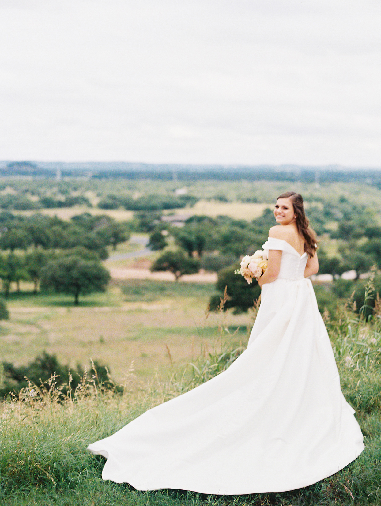 bride smiling looking back over her shoulder next to grassy hillside