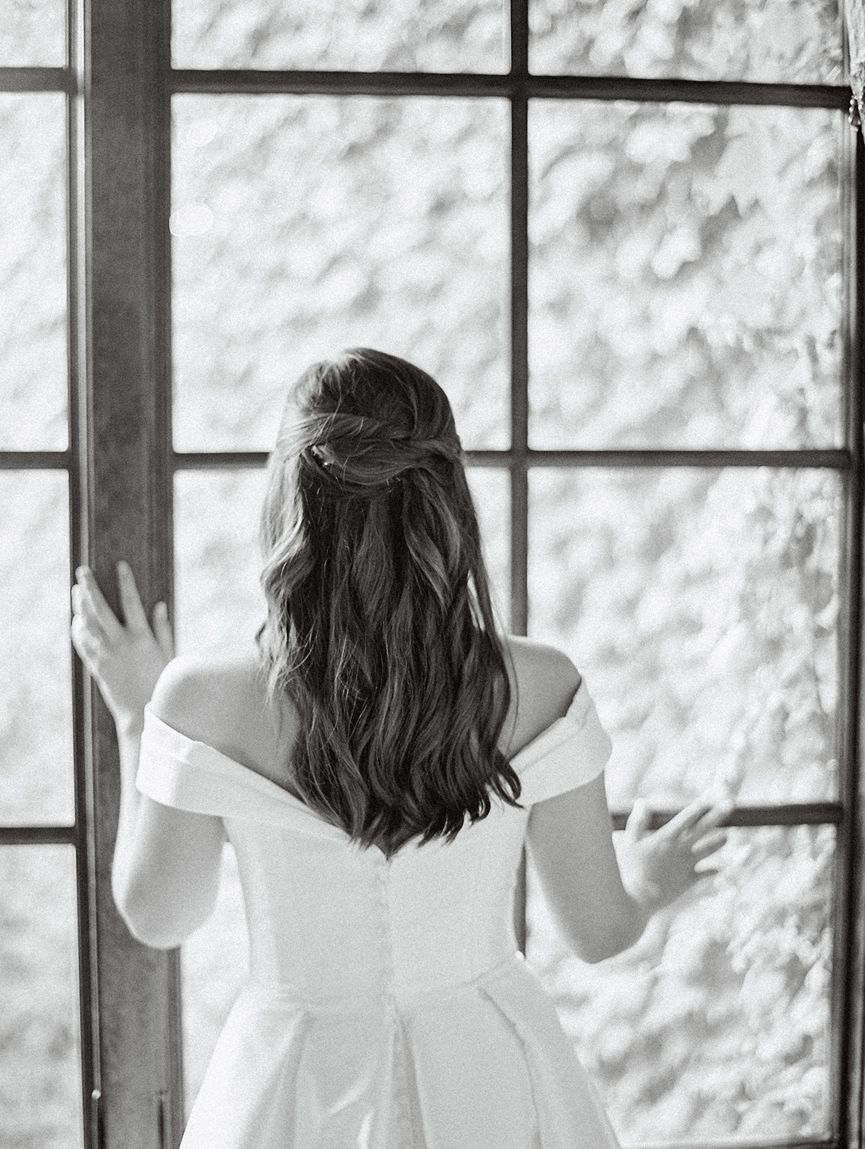 bride facing window with hands on frame