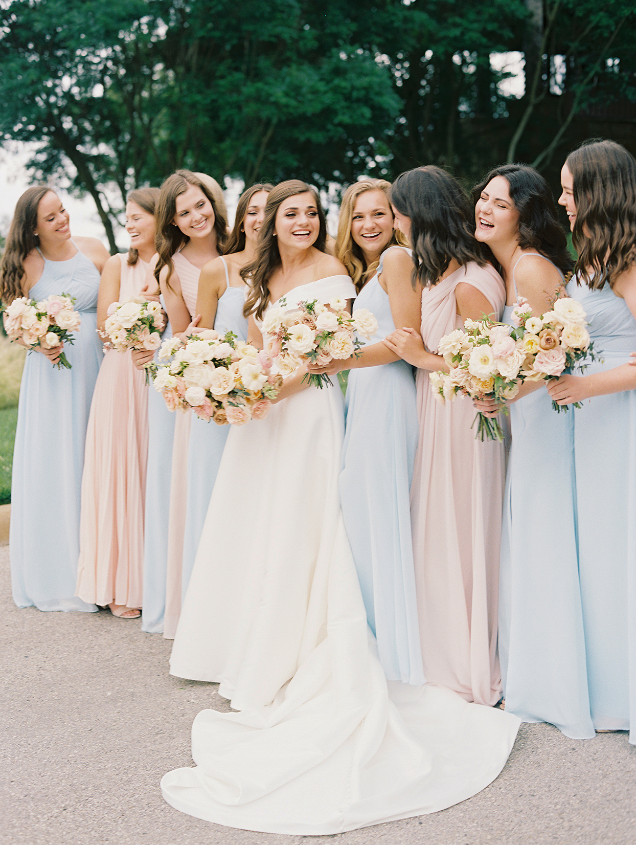 bride smiling with her bridesmaids wearing pink and blue dresses