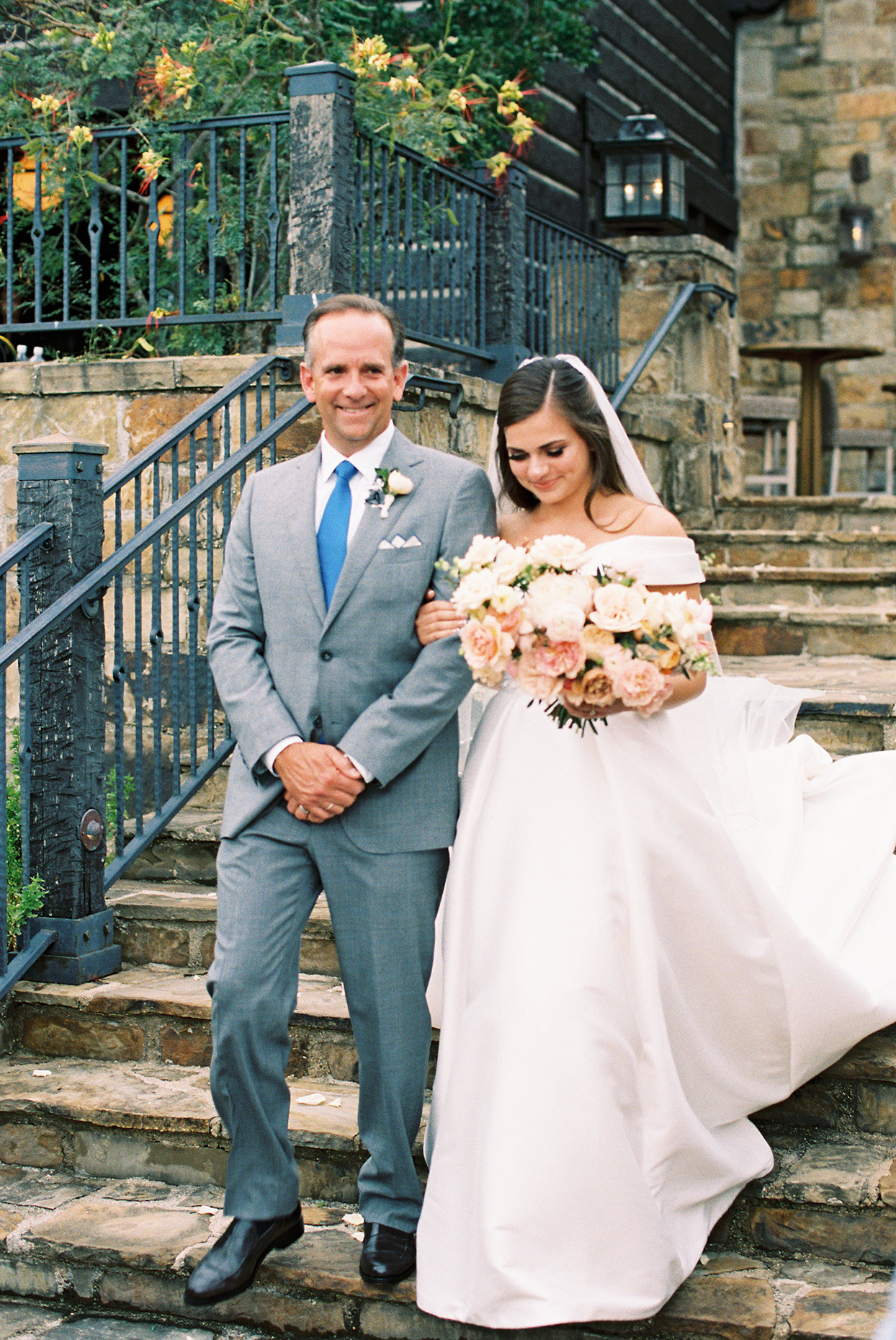 bride walking with her dad down the stairs holding his arm