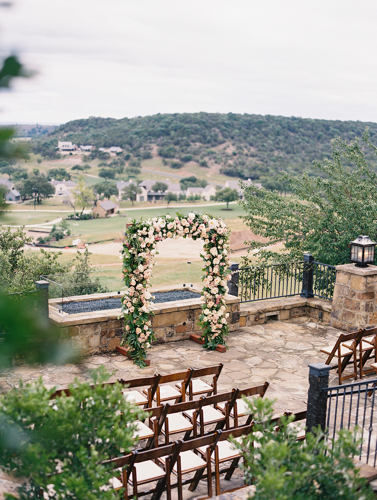 wedding ceremony space with wood chairs and pink floral arch