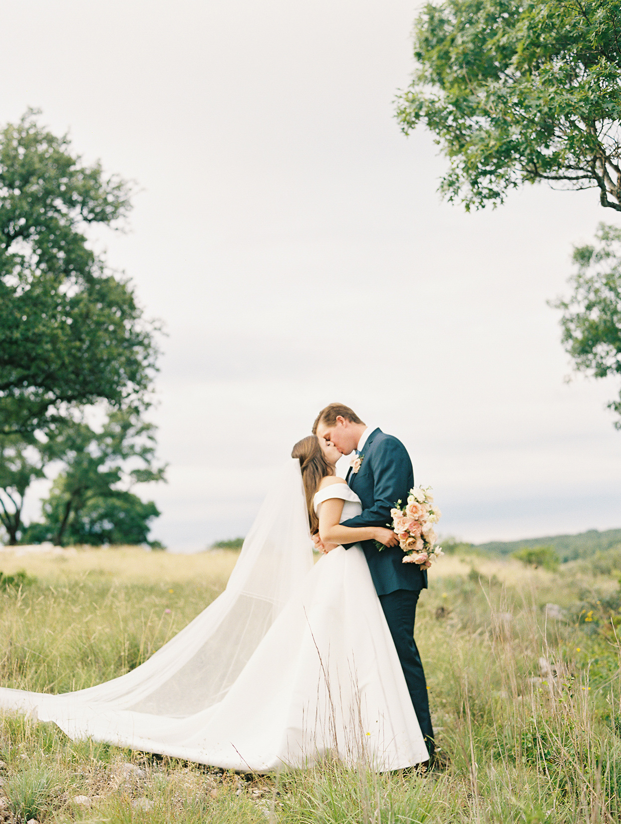 bride and groom kiss on grassy hillside