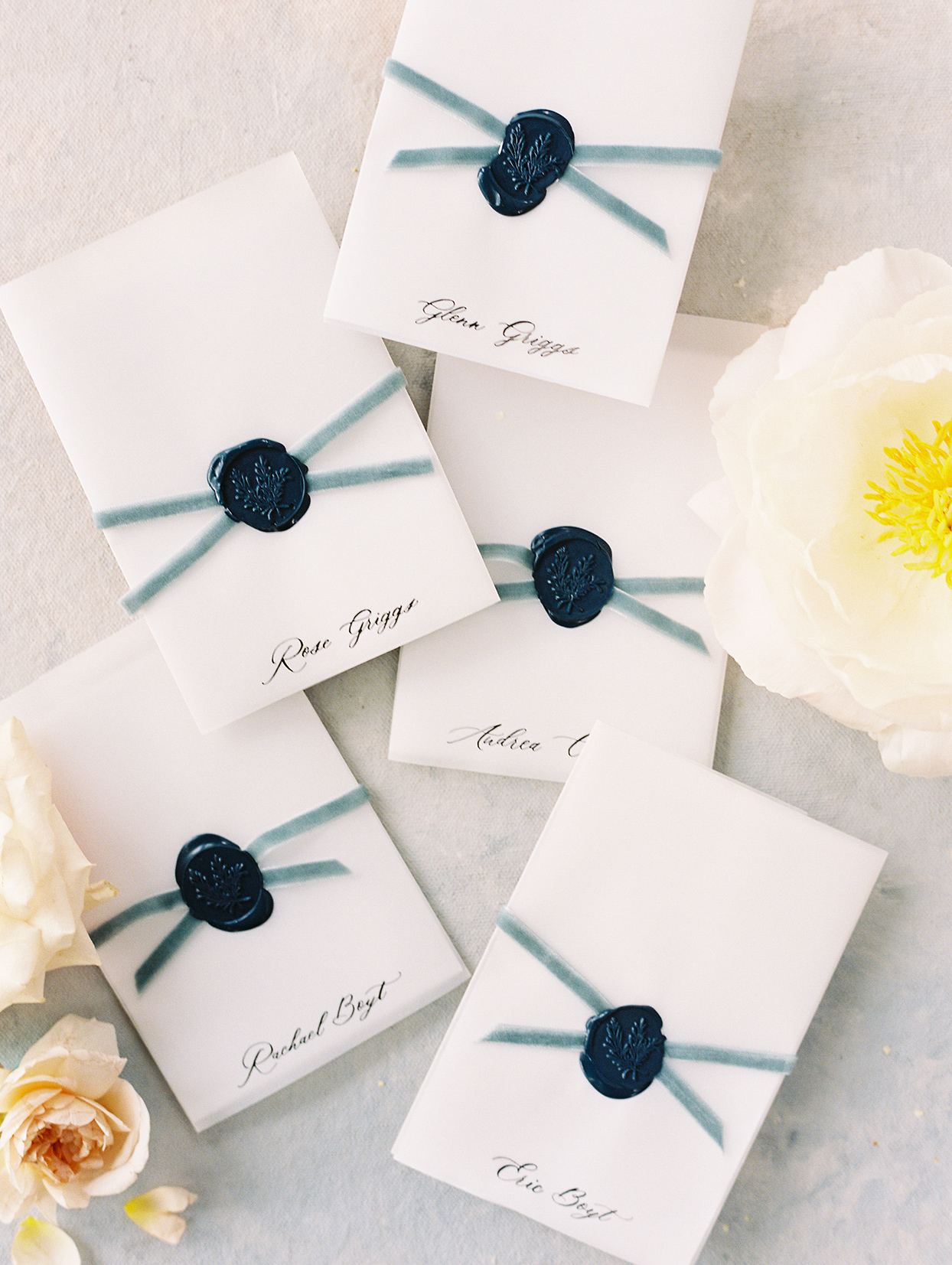 white escort cards with blue wax stamp