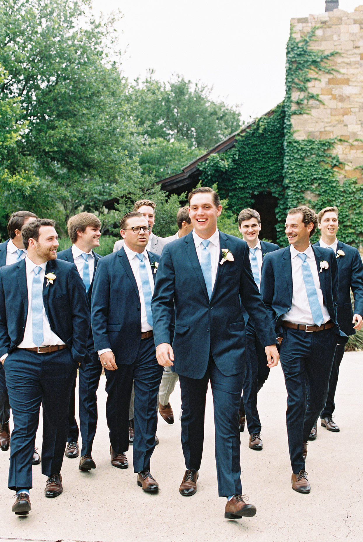 groom walking with groomsmen wearing matching blue suits