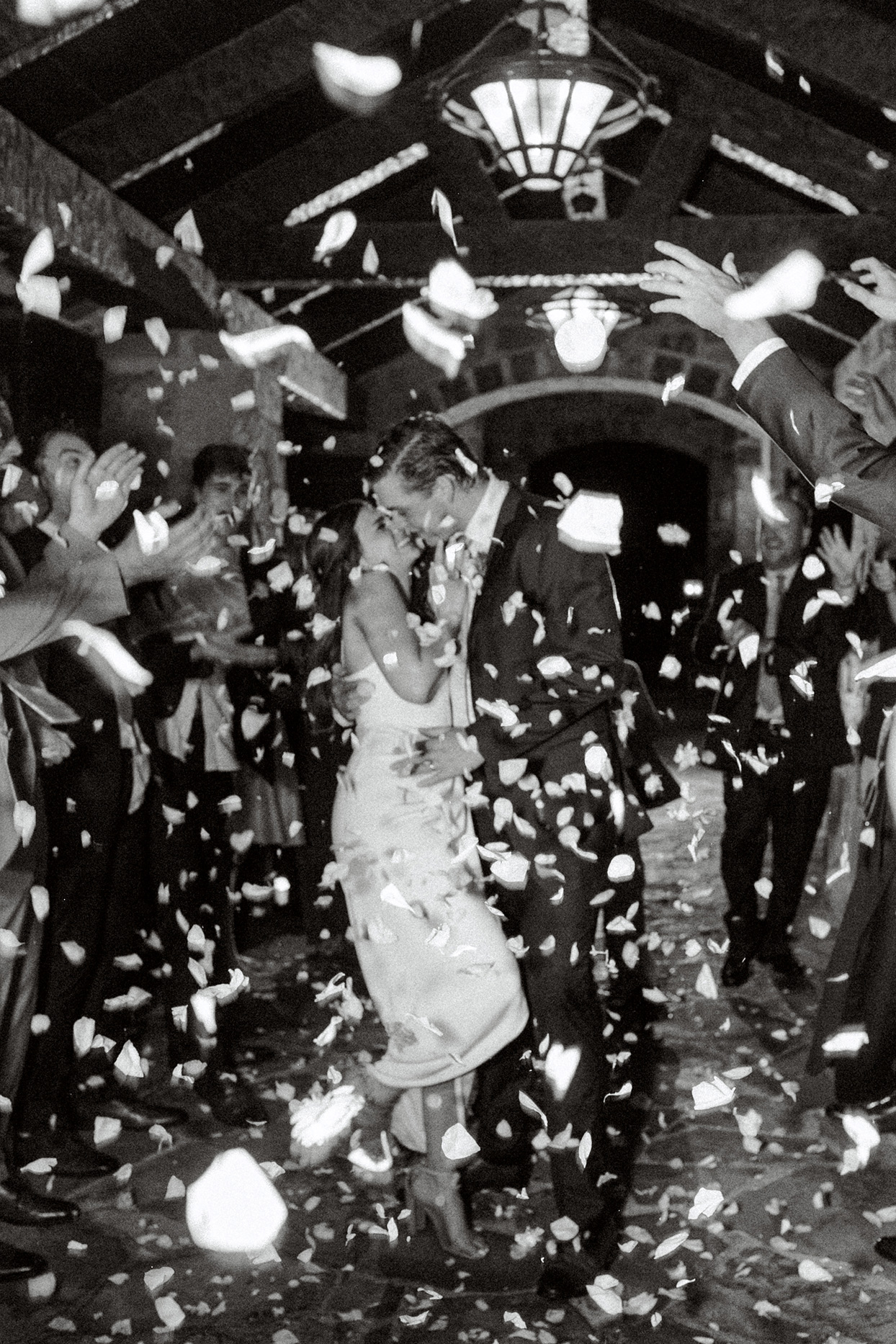 bride and groom embrace under shower of confetti thrown by guests