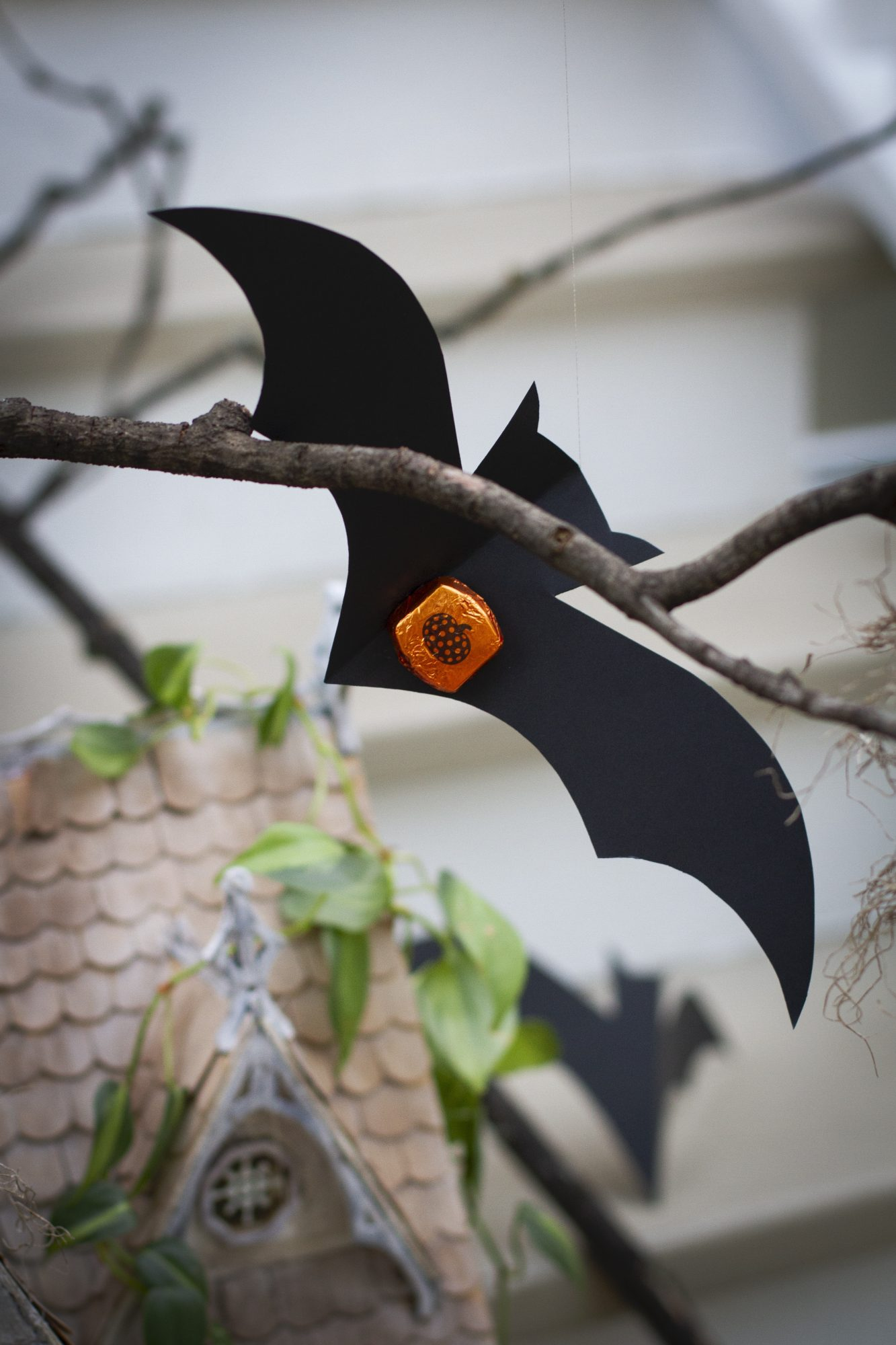 paper bat suspended above a miniature haunted house