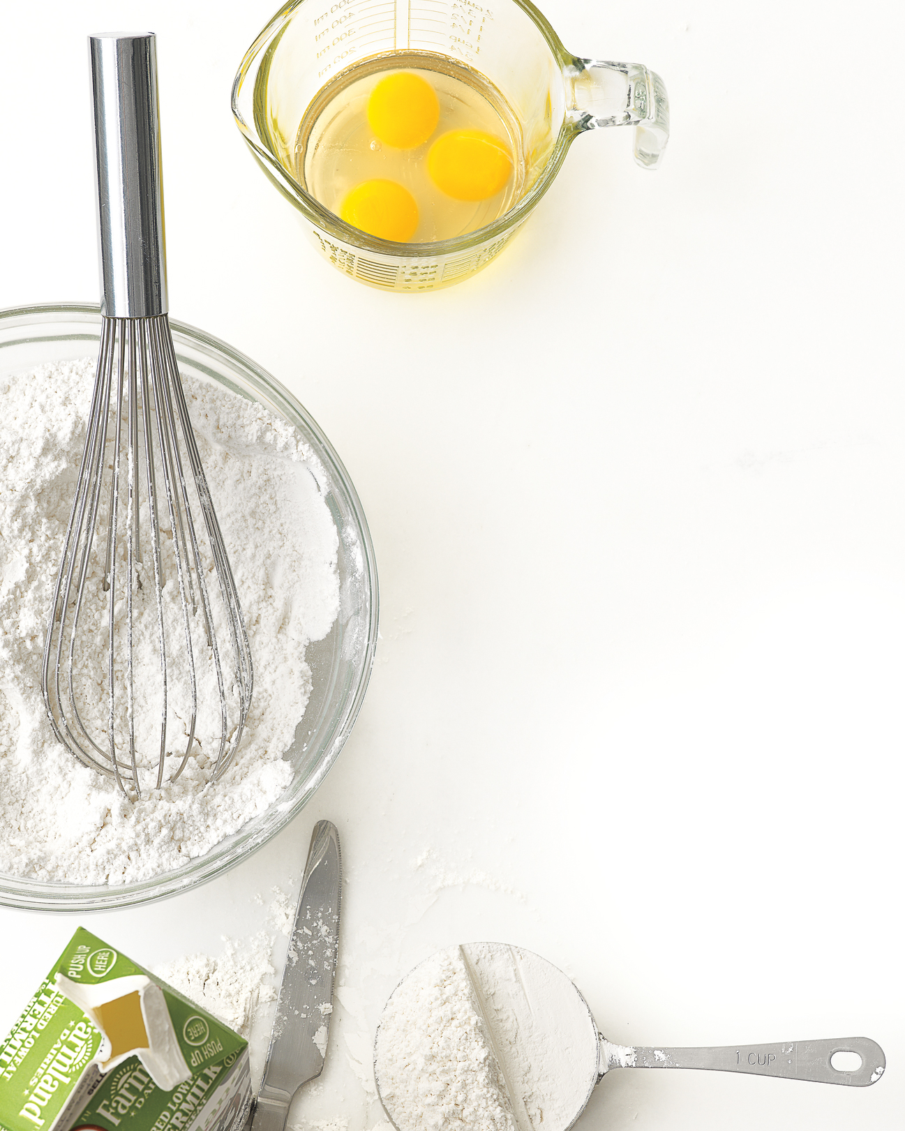 eggs in glass measuring cup, flour in a bowl and in a measuring cup, and buttermilk in a carton