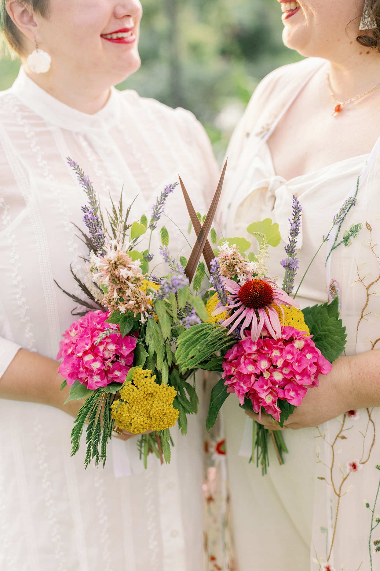 brides smiling holding floral bouquets from their garden