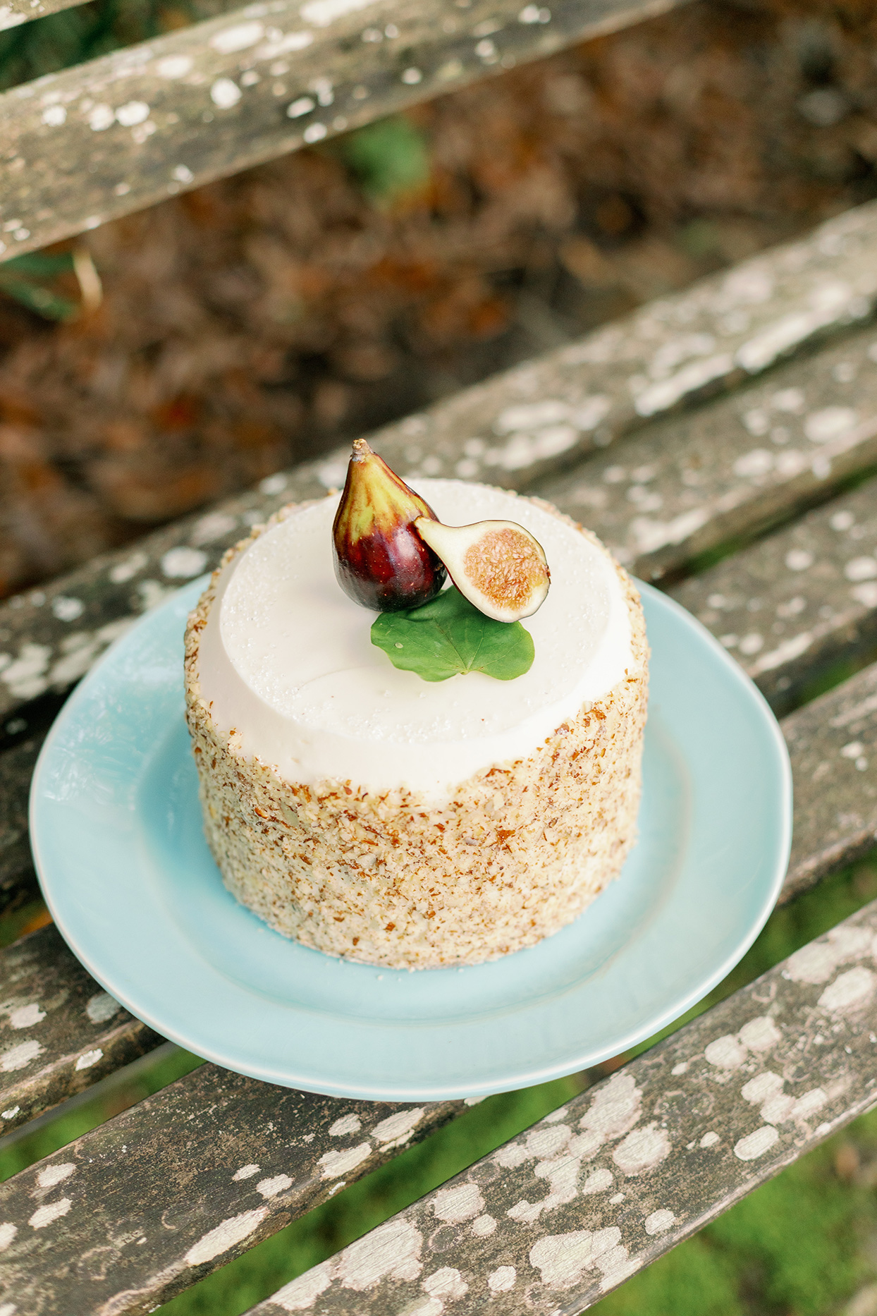 fig topped single layer round wedding cake on blue plate