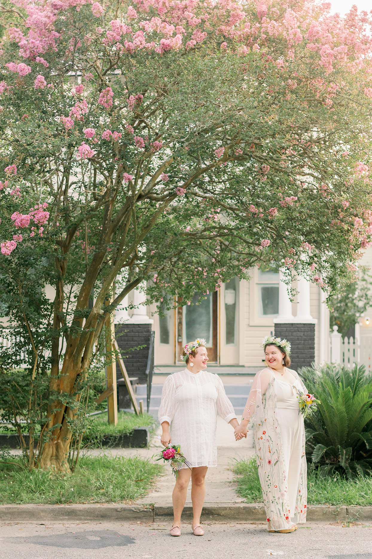 brides standing on street under pink floral tree