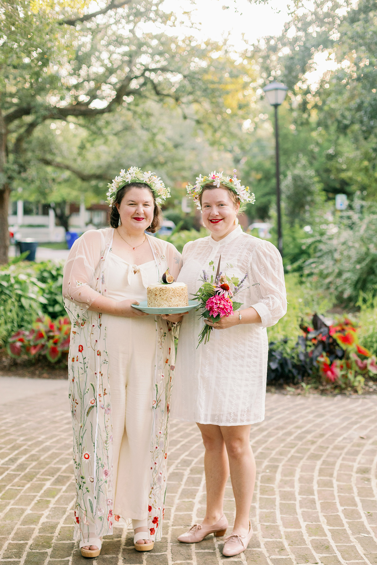brides smiling holding cake and flowers