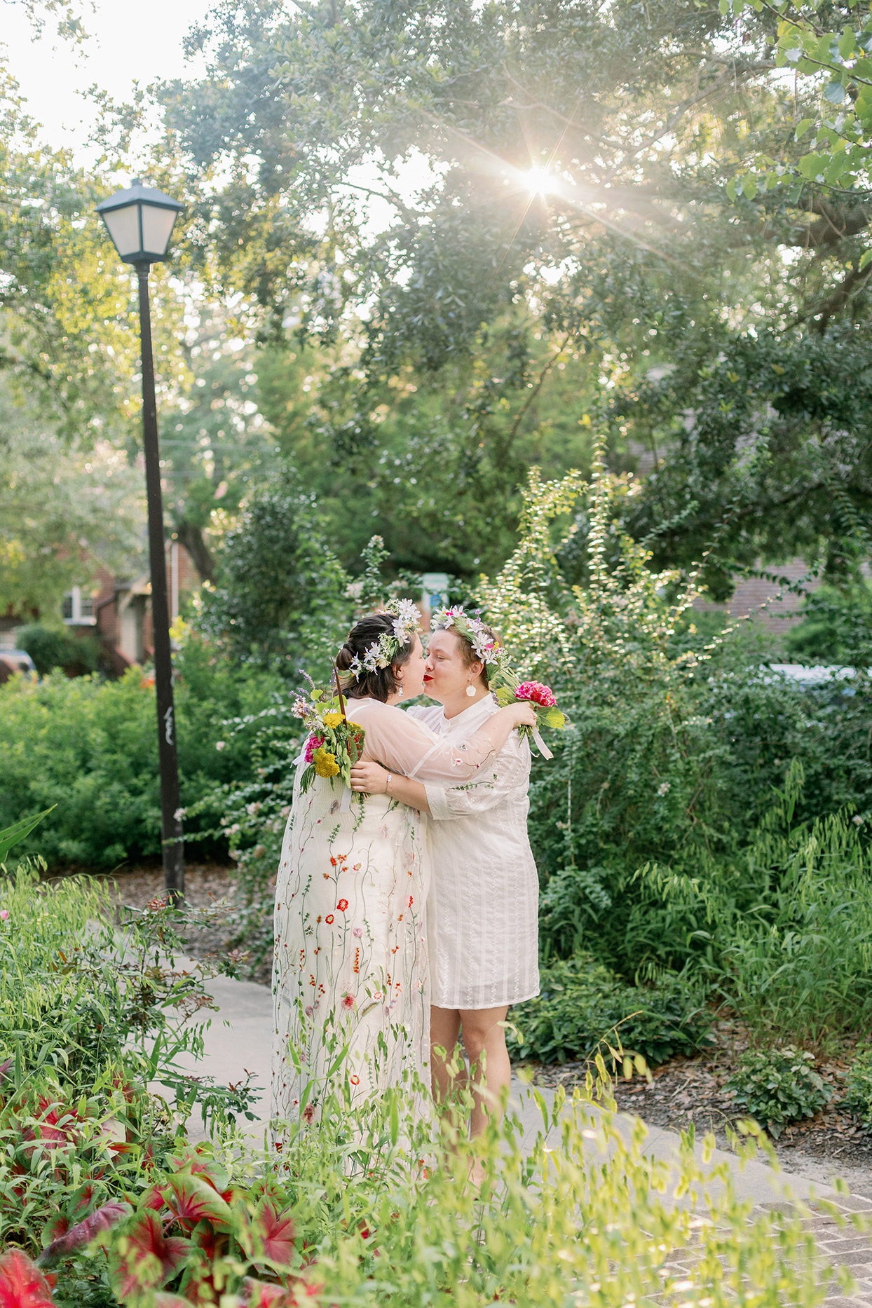 brides sharing a kiss on outdoor paved path