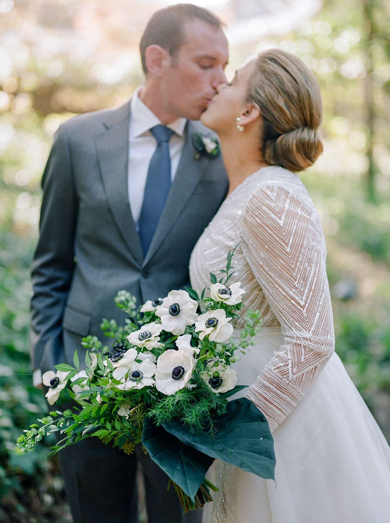 bride and groom kissing while bride holds black and white floral wedding bouquet