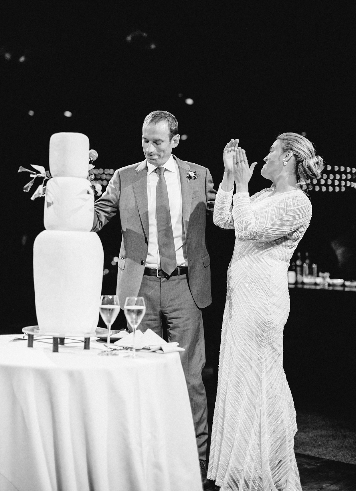 bride and groom standing next to tall three layer wedding cake