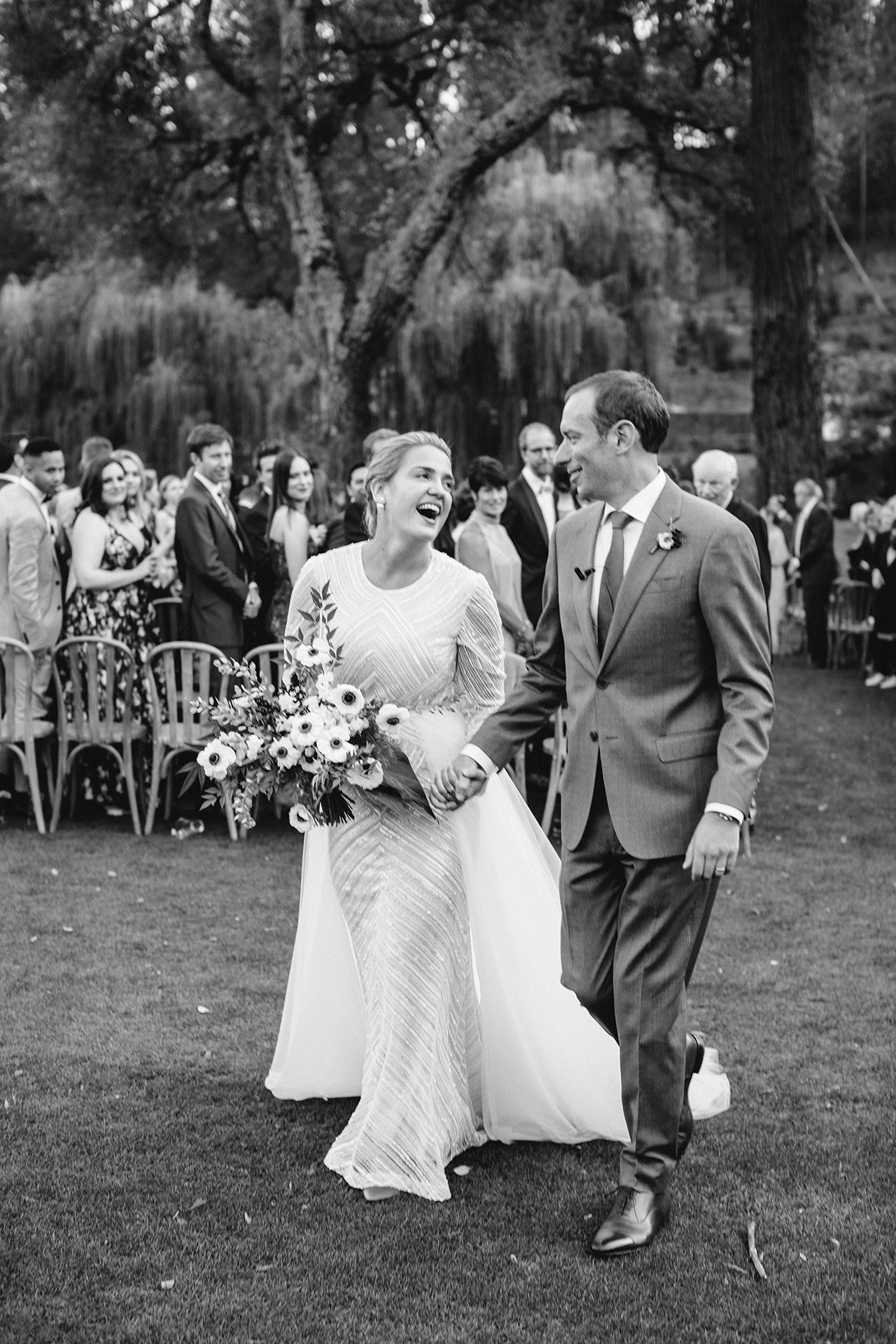bride and groom smiling holding hands after recessional
