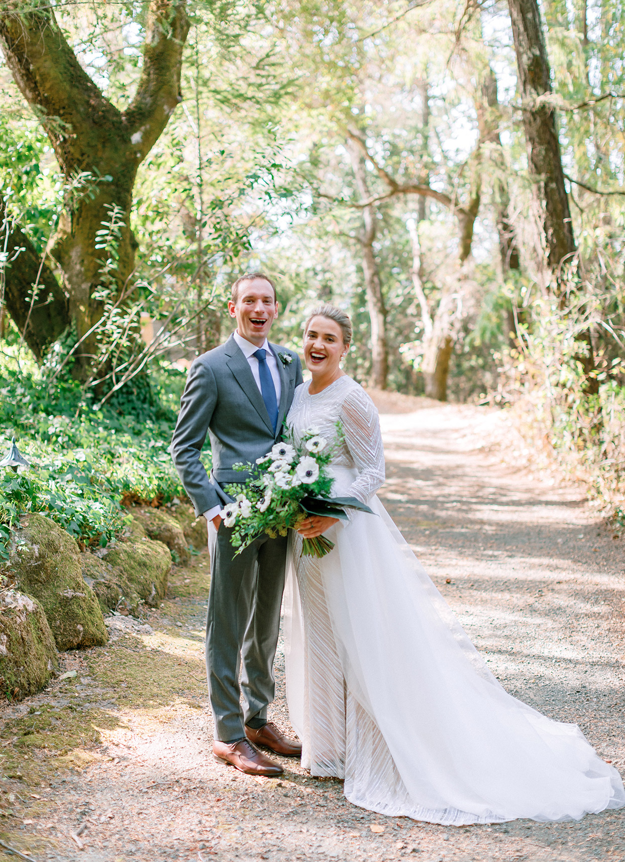bride and groom with open mouth smiles on outdoor trail
