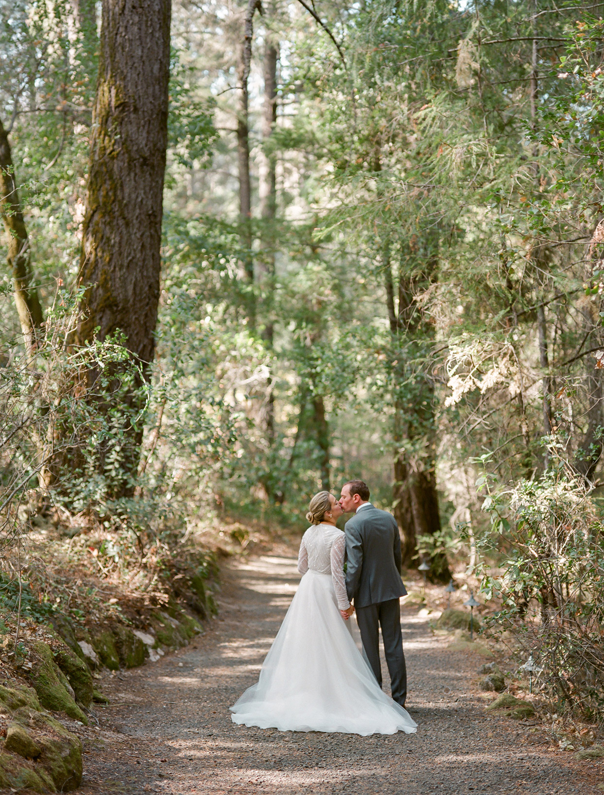 bride and groom kiss standing on outdoor trail