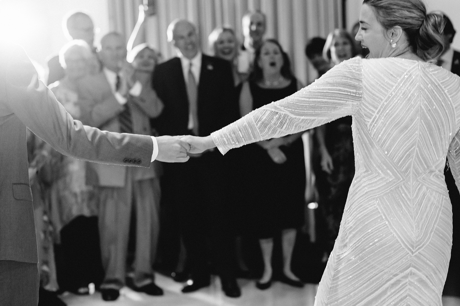 bride and groom hold hands during first dance as guests watch