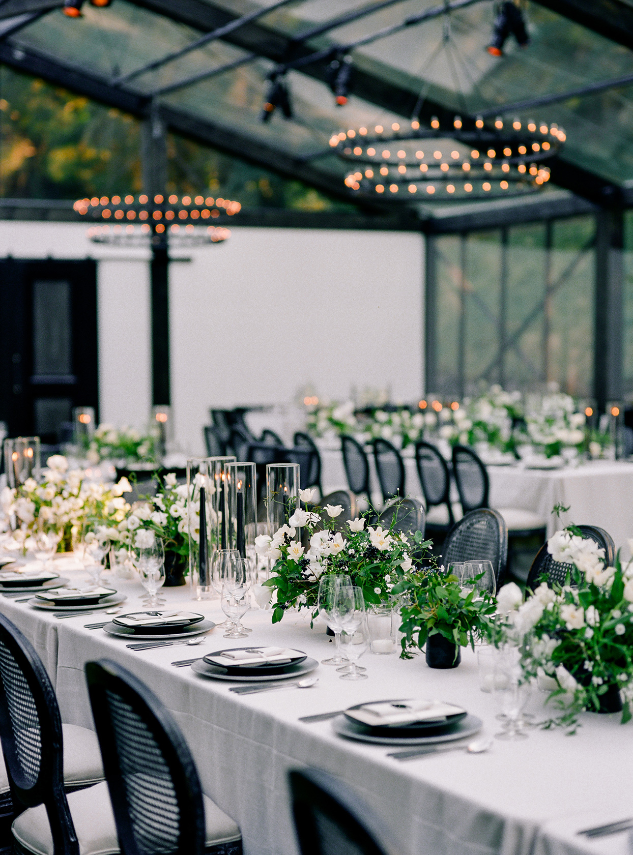 black and white themed long reception tables with overhead lighting