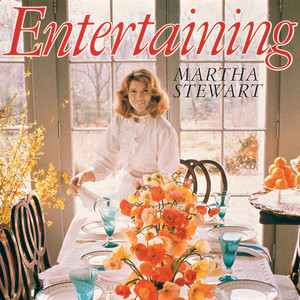 martha stewart decorating a dining table with place settings and bright flowers
