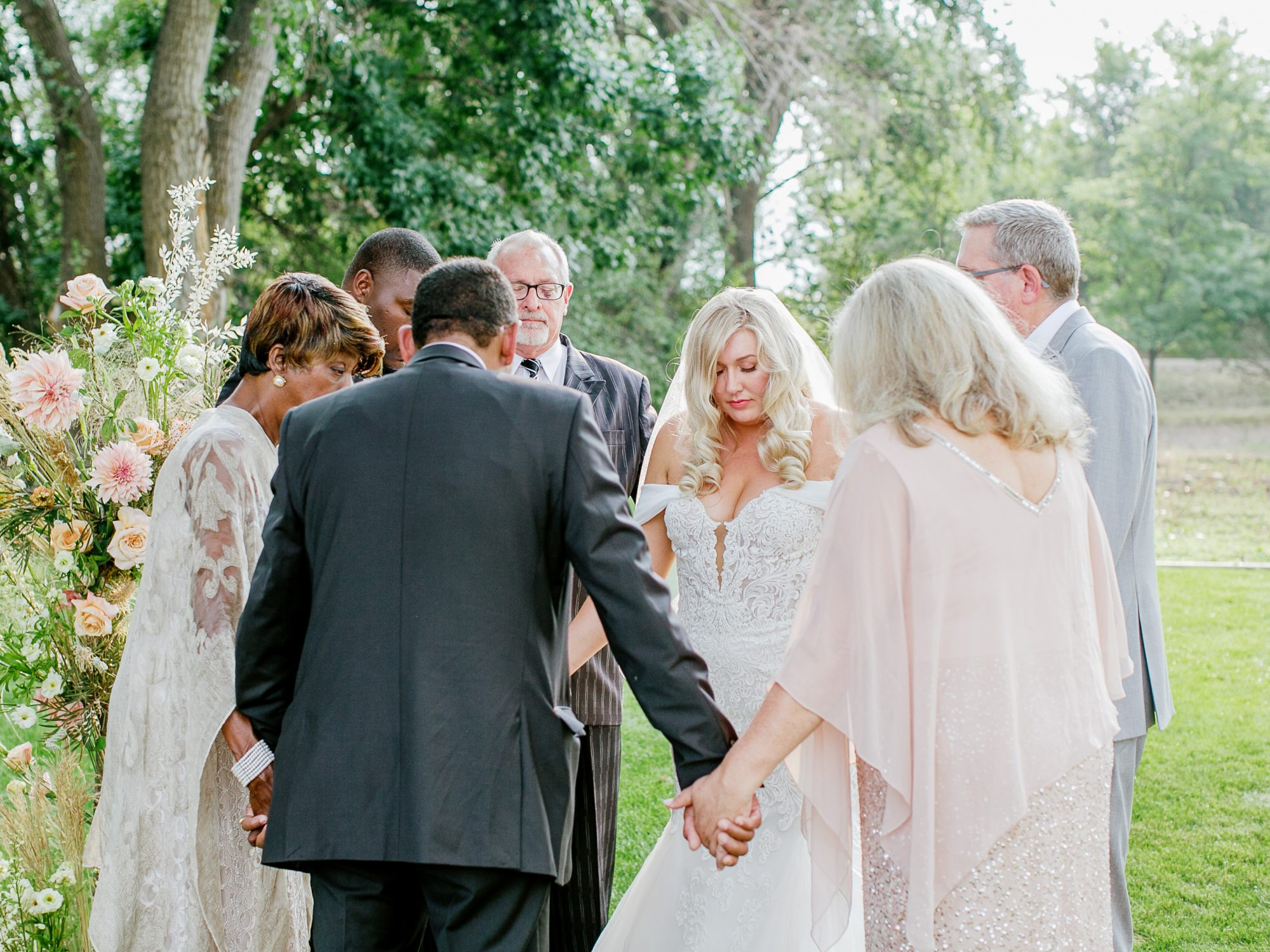 family holding hands during wedding ceremony