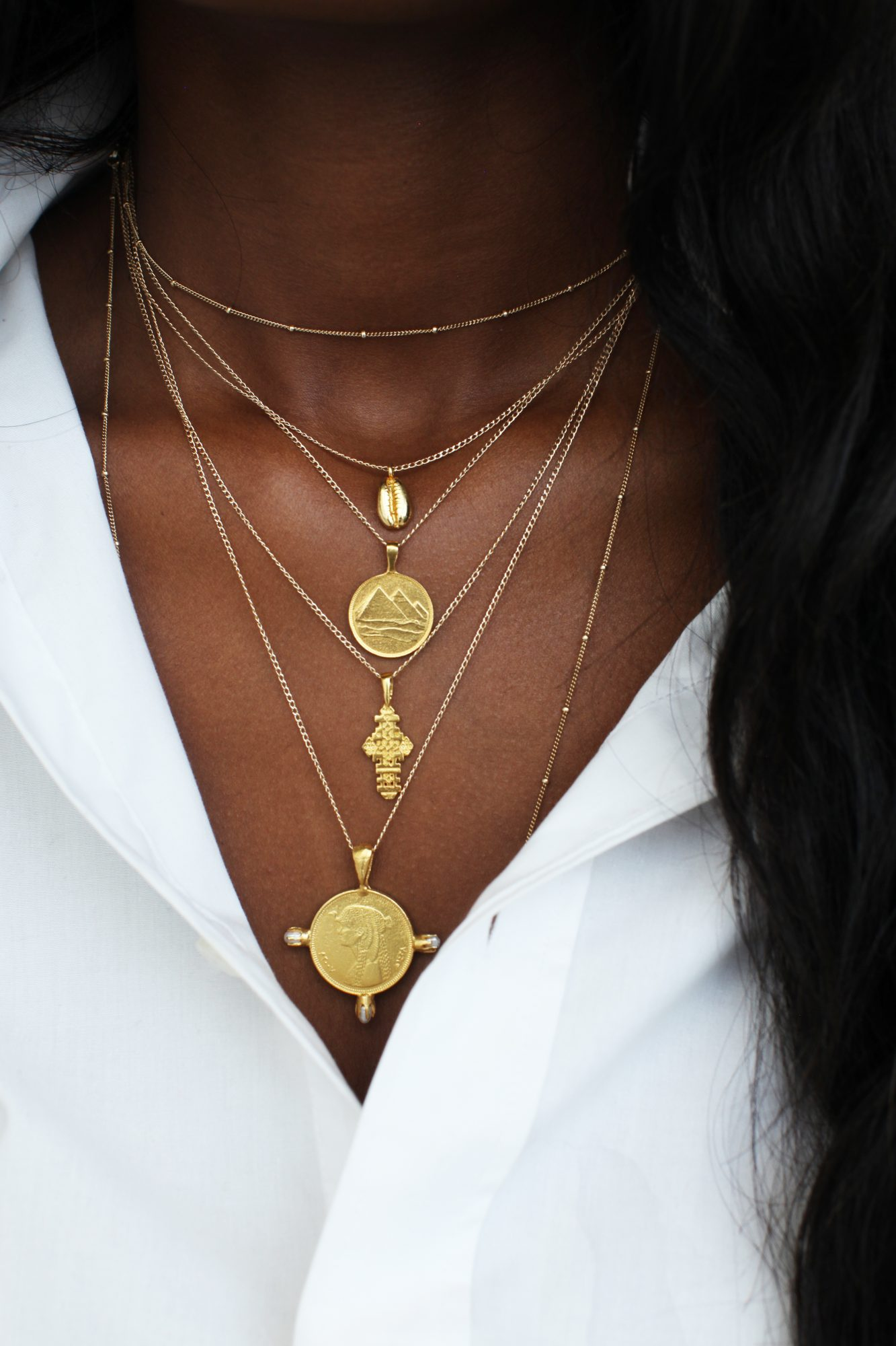cowrie and cross layered necklace by Omi Woods