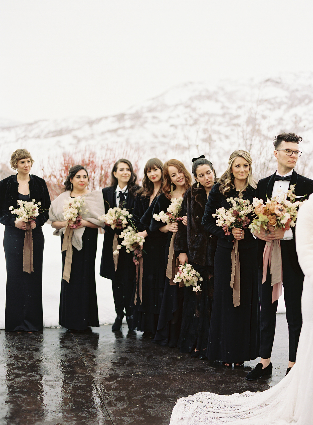 bridesmaids during wedding ceremony outside snowing while wearing black