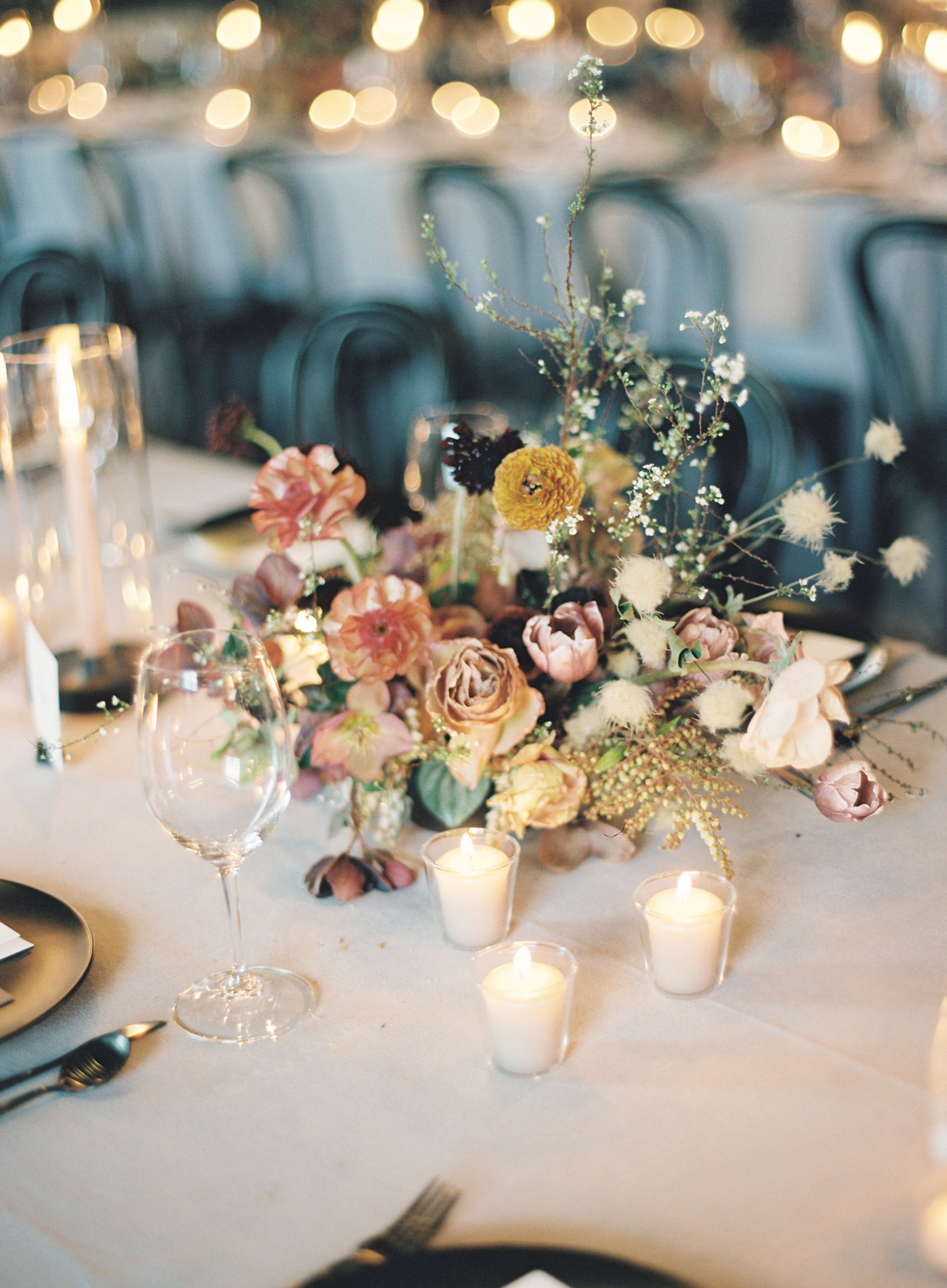 various color and style floral centerpiece surrounded by low candles