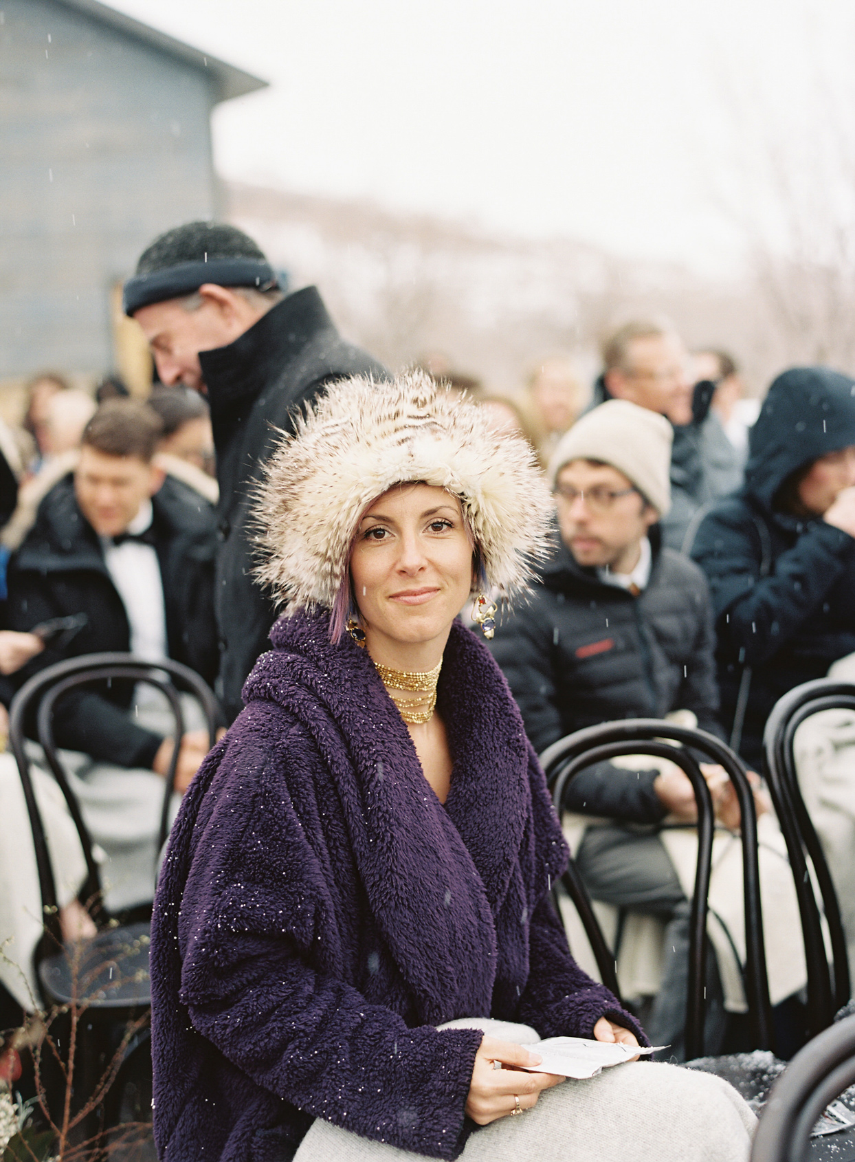 wedding guests wearing furry hat and purple coat
