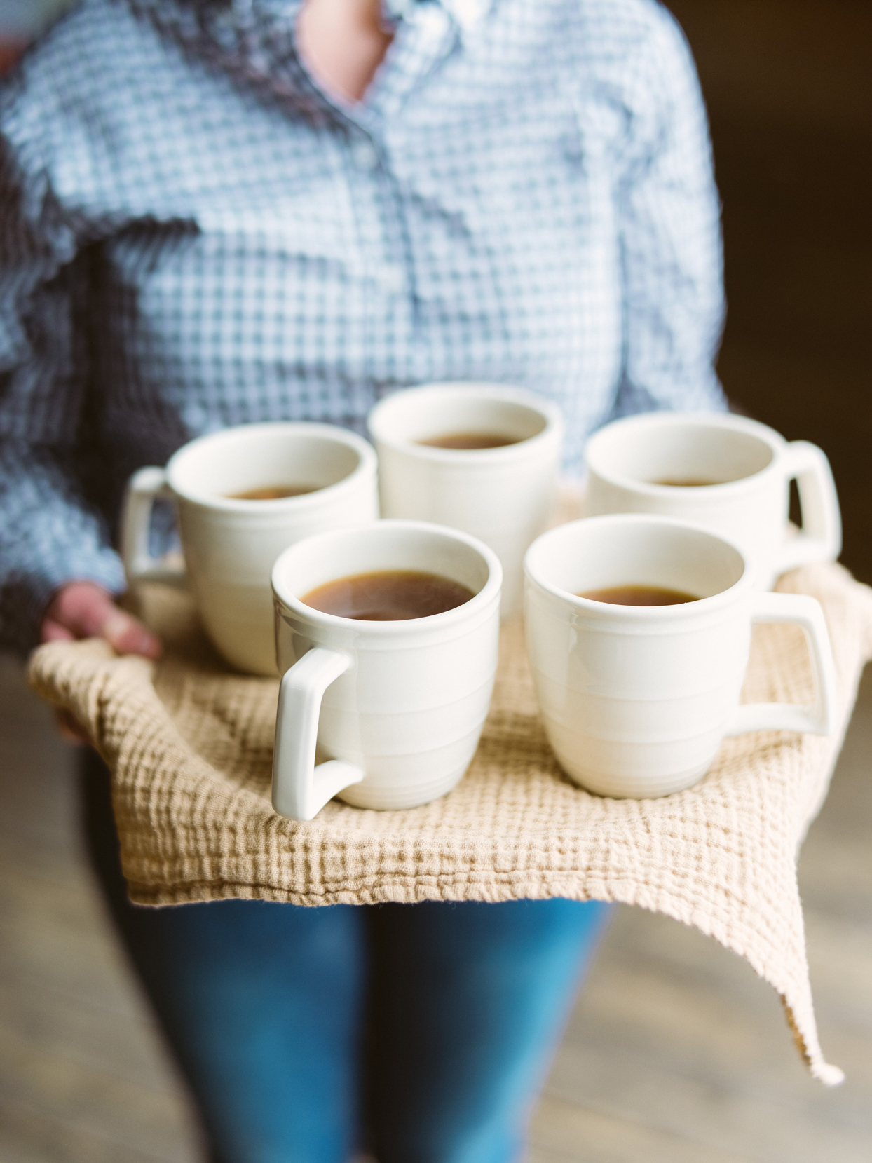 apple cider in white mugs on tray covered in tan linen