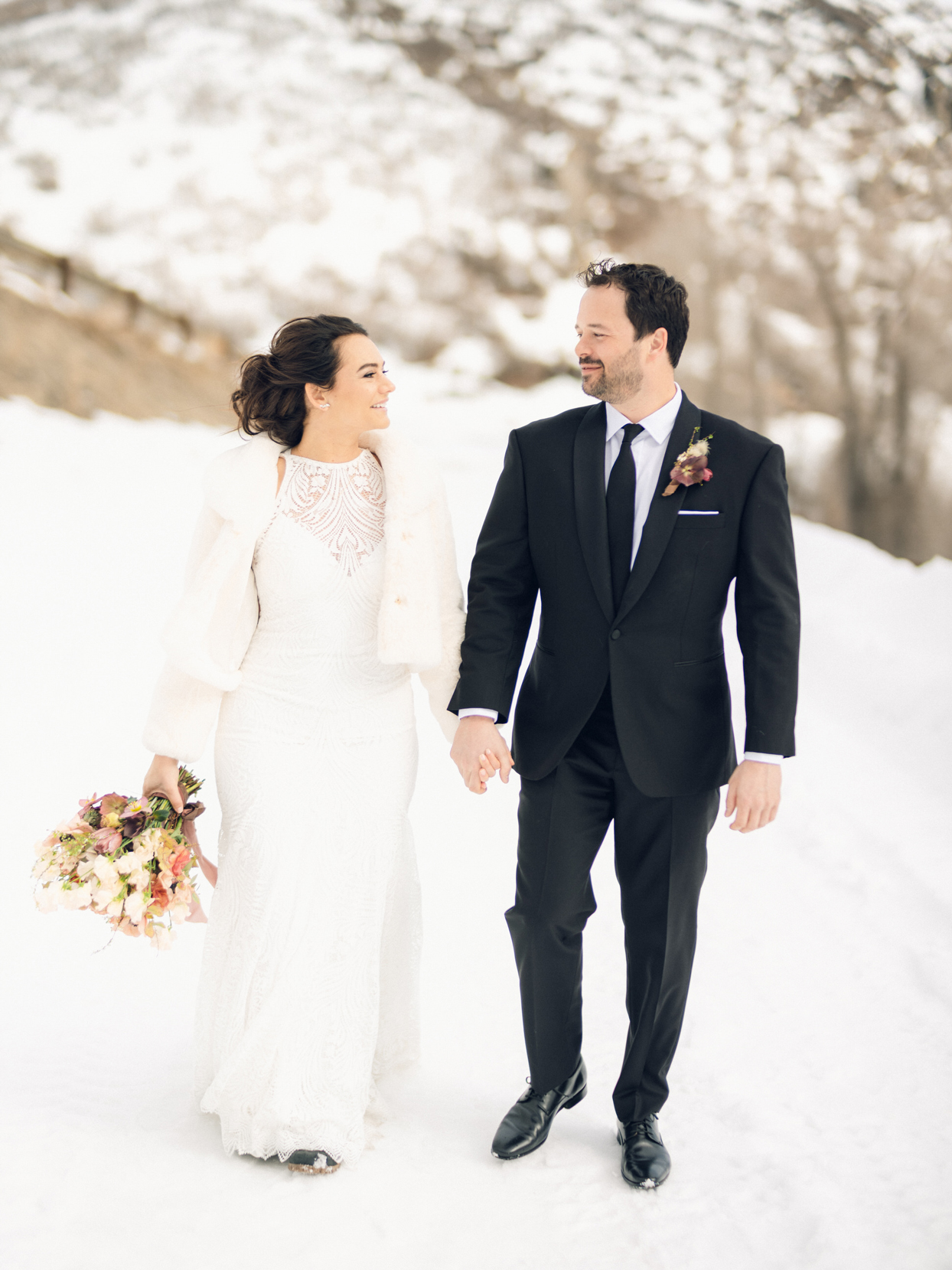 bride and groom hold hands smiling outside in the snow